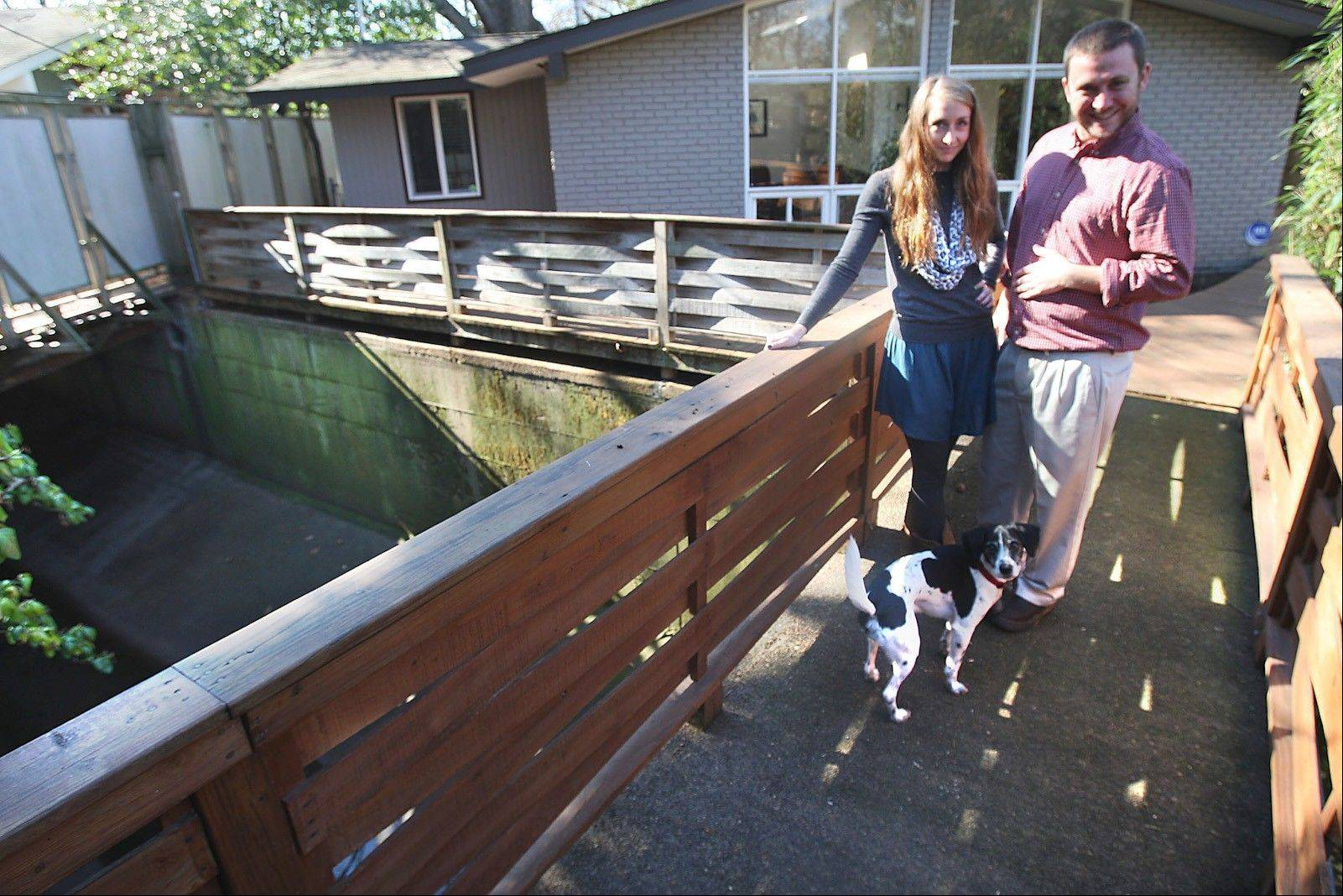 Cate and Paul Plekon and their dog Sampson stand on a bridge in front of their home, which borders a concrete drainage ditch that carries Cypress Creek through the Memphis neighborhood.