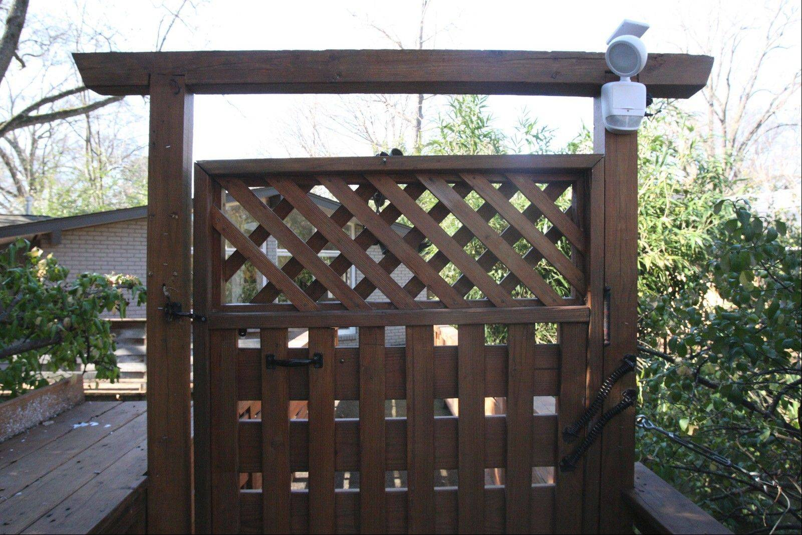 A wooden gate in front of the Plekon home serves as an entrance to the property where the bridge meets the sidewalk and a parking area. It reflects a Japanese style incorporated into the landscaping.