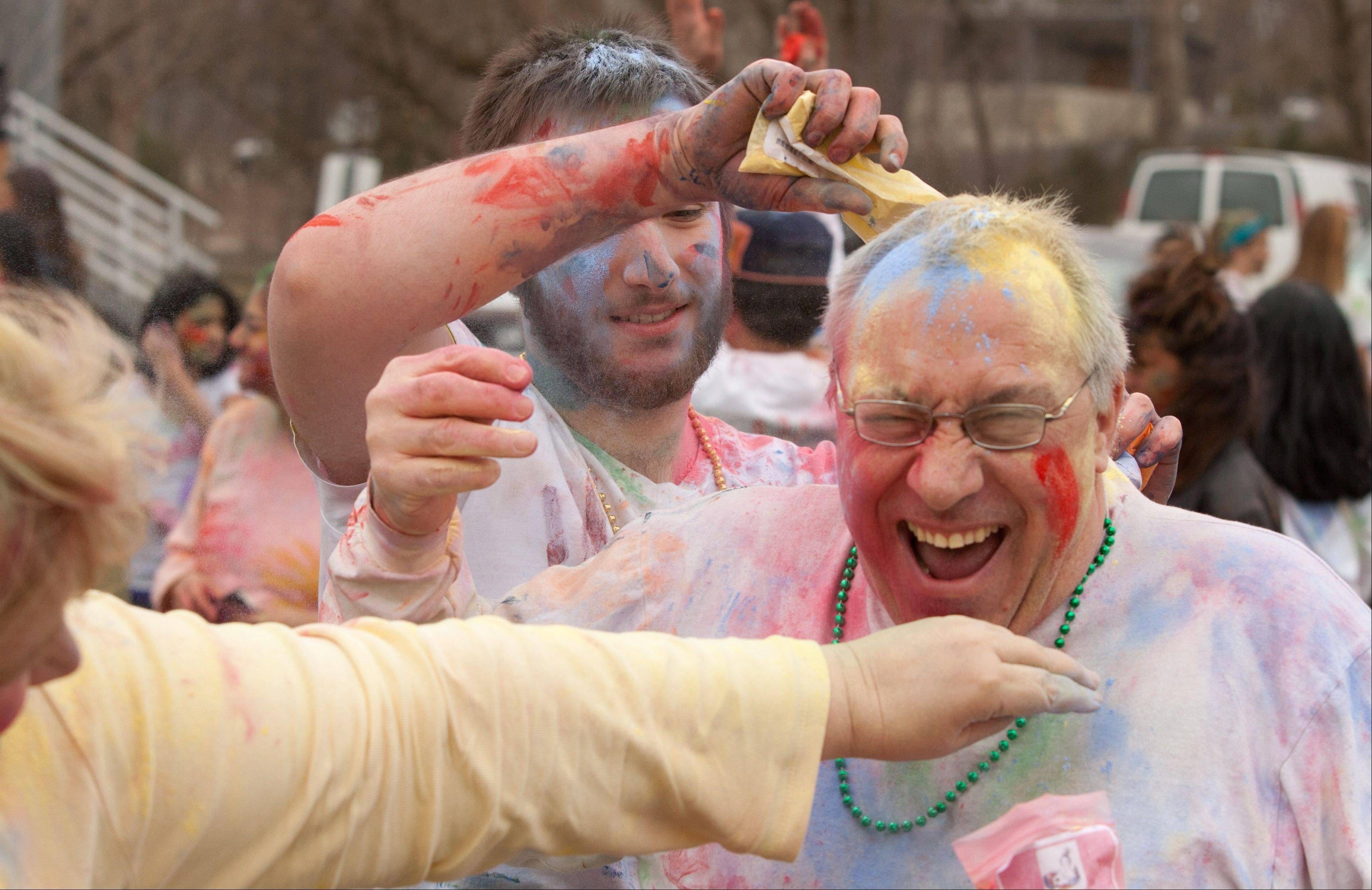 Karl Michalec of Elk Grove gets showered in yellow flour by his son, Ian, and wife, Jeanie, on Saturday in Naperville during the Simply Vedic Cultural Society's Festival of Colors, a celebration of the Hindu festival that marks the passing of winter and arrival of spring.
