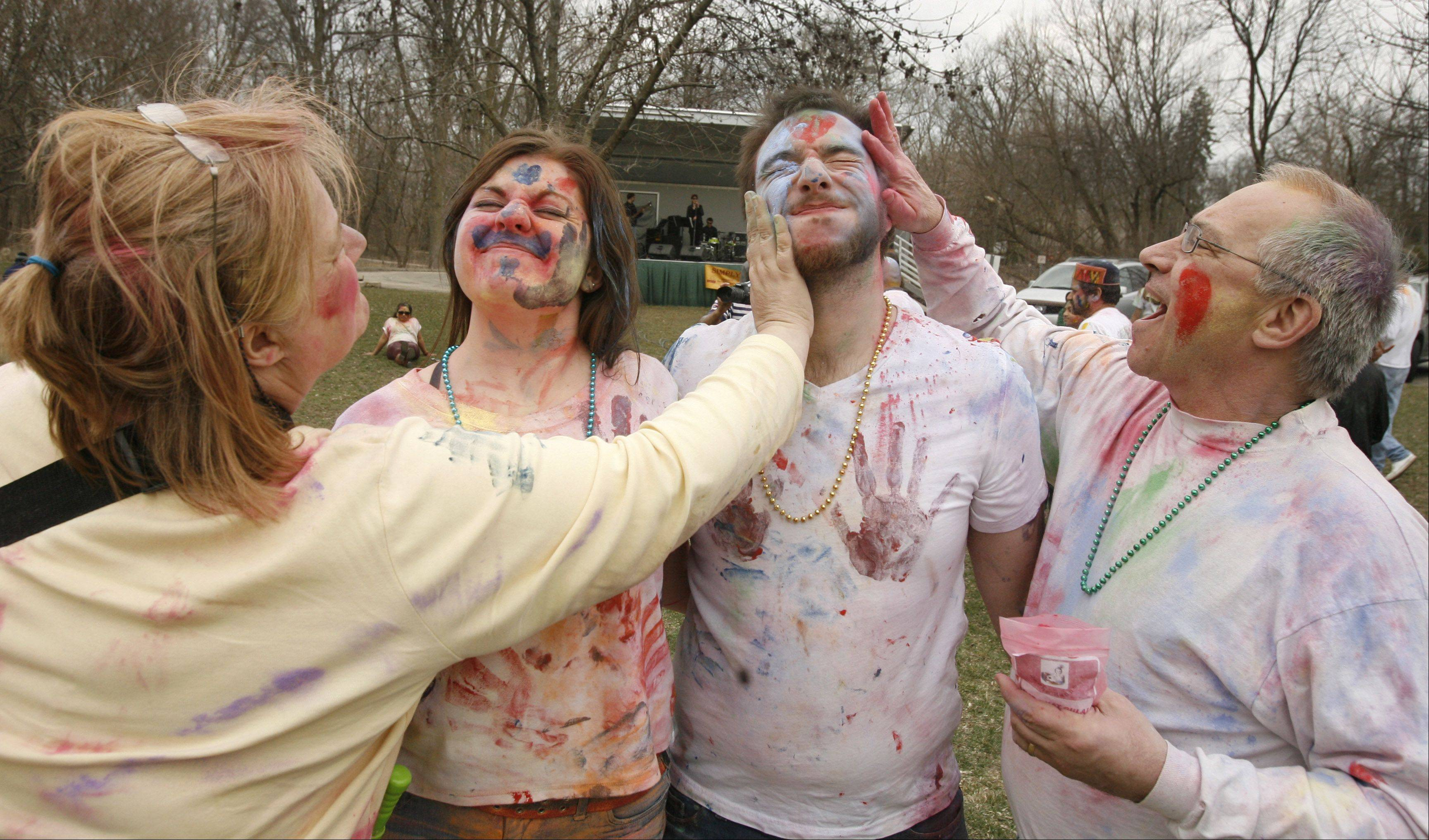 Jeanie and Karl Michalec of Elk Grove spread color on their son Ian's face while Jamie Hicks waits her turn Saturday as they celebrate the coming of spring at the Simply Vedic Cultural Society's annual Festival of Colors in Naperville.