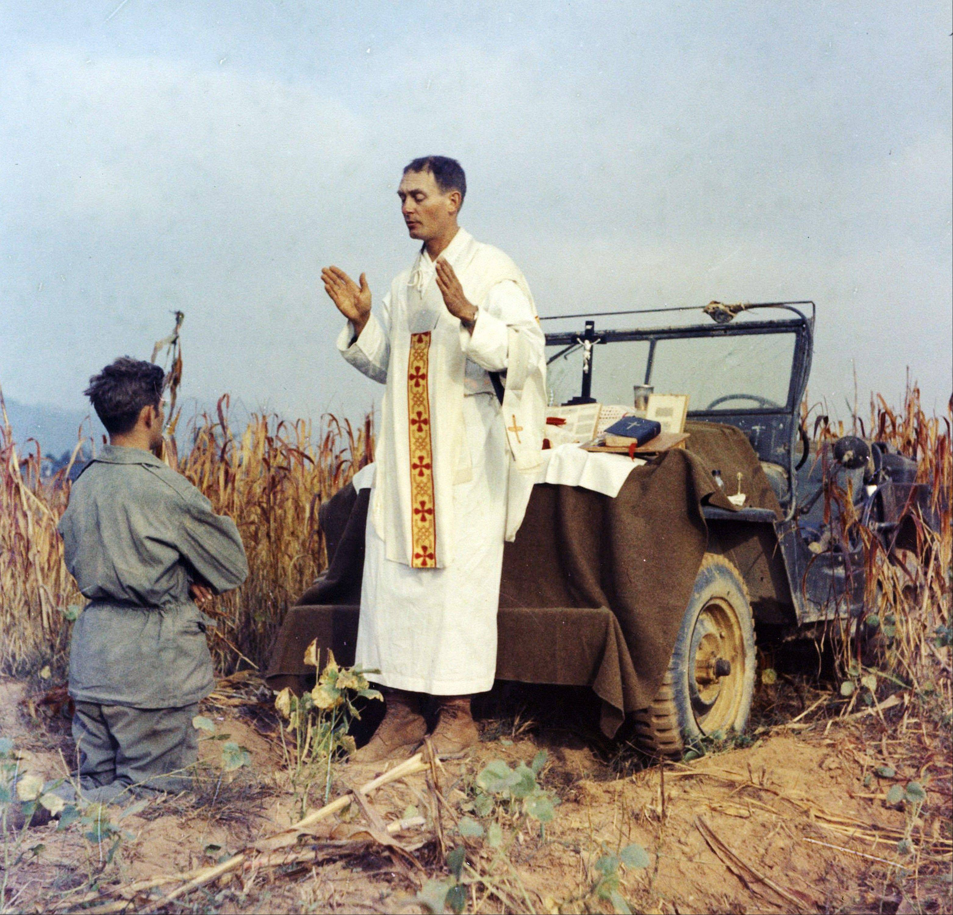 In this photo provided by Col. Raymond A. Skeehan, Father Emil Kapaun celebrates Mass using the hood of his jeep as an altar, as his assistant, Patrick J. Schuler, kneels in prayer in Korea on Oct. 7, 1950, less than a month before Kapaun was taken prisoner. Kapaun died in a prisoner of war camp on May 23, 1951, his body wracked by pneumonia and dysentery. On April 11, 2013, President Barack Obama will award the legendary chaplain, credited with saving hundreds of soldiers during the Korean War, the Medal of Honor posthumously.