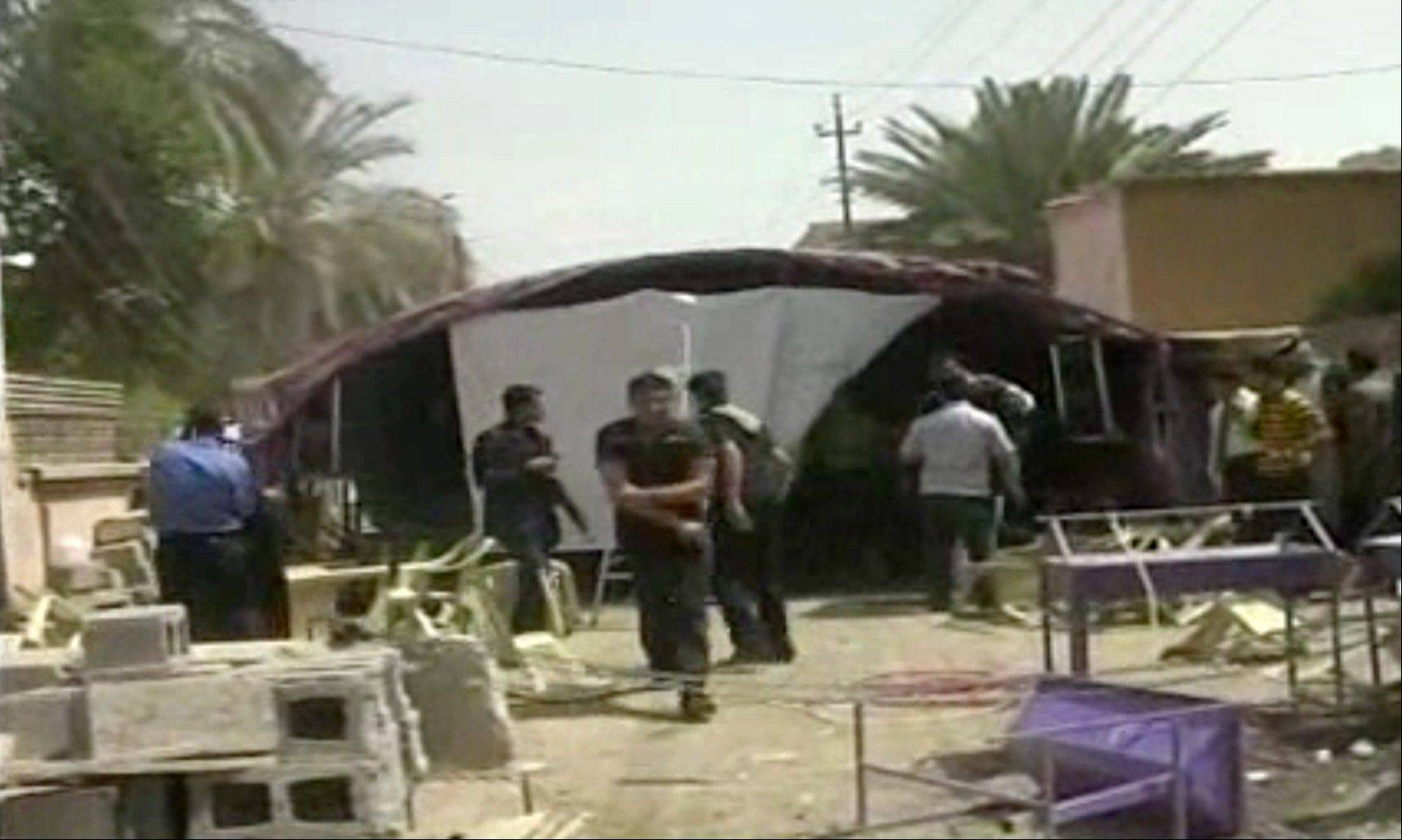 This image from AP video shows the aftermath of a suicide attack in Baqouba, some 35 miles northeast of Baghdad, Iraq, Saturday, April 6, 2013. A suicide bomber blew himself up Saturday at a lunch hosted by a Sunni candidate in Iraq's upcoming regional elections, killing scores of people, officials said. The blast ripped through a hospitality tent pitched next to the house of Muthana al-Jourani, who is running for the provincial council and held the lunch rally for supporters, councilman Sadiq al-Huseini said.