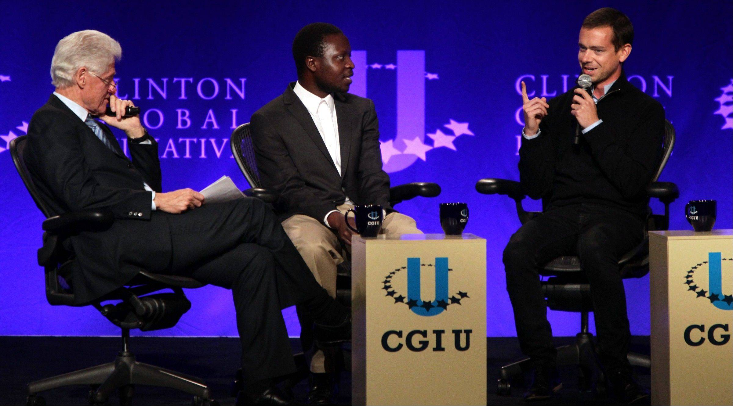 Former President Bill Clinton, left, listens as Twitter co-founder Jack Dorsey, right, explains his work with Square during the opening session of the Clinton Global Initiative at Washington University in St. Louis on Friday, April 5. Malawian inventor William Kamkwamba listens at center.