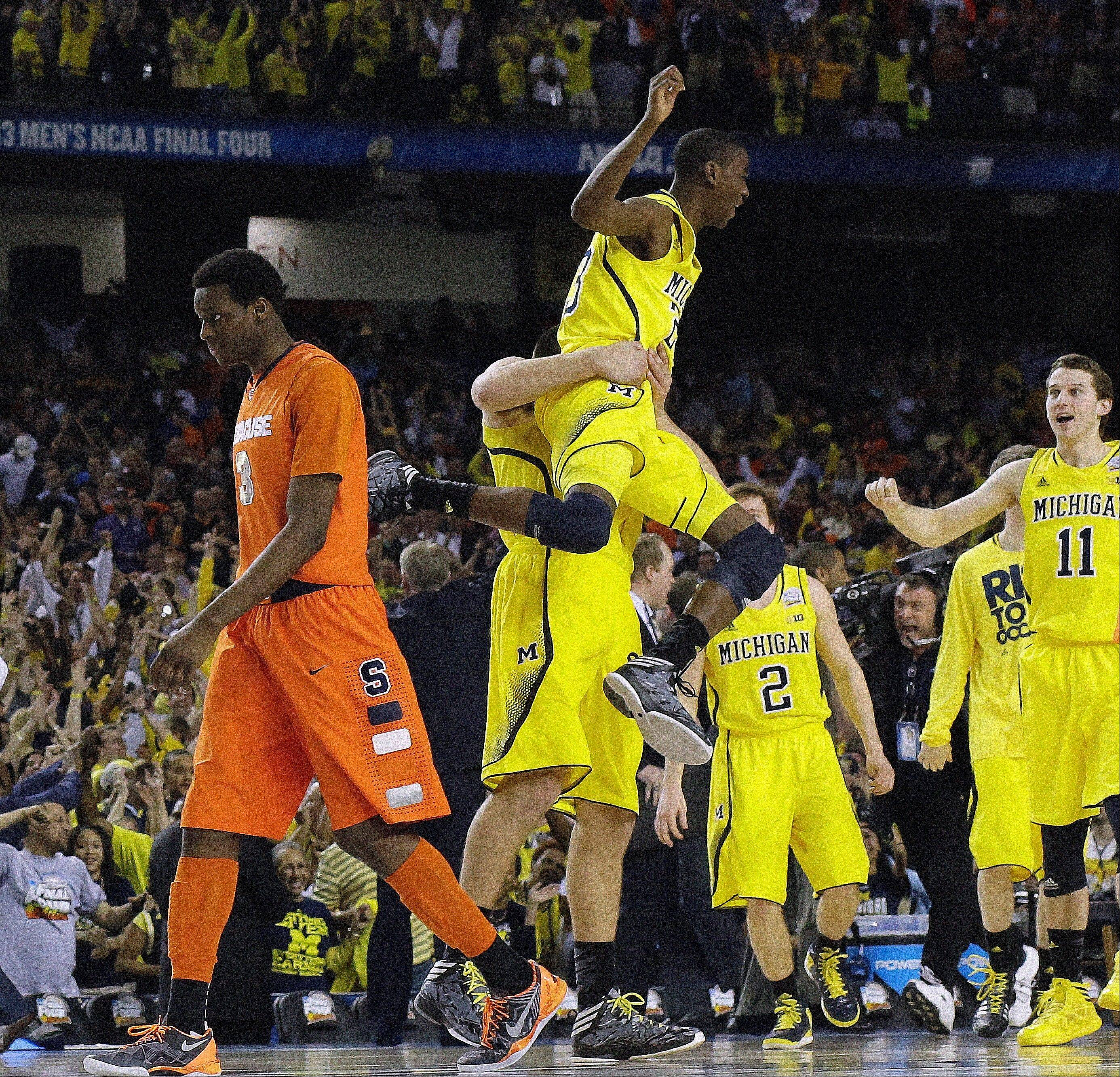 Michigan's Caris LeVert (23) celebrates with team mates as Syracuse's Jerami Grant (3) walks off the court after the Wolverines defeated the Orangemen Saturday to earn a trip to Monday's NCAA title game.