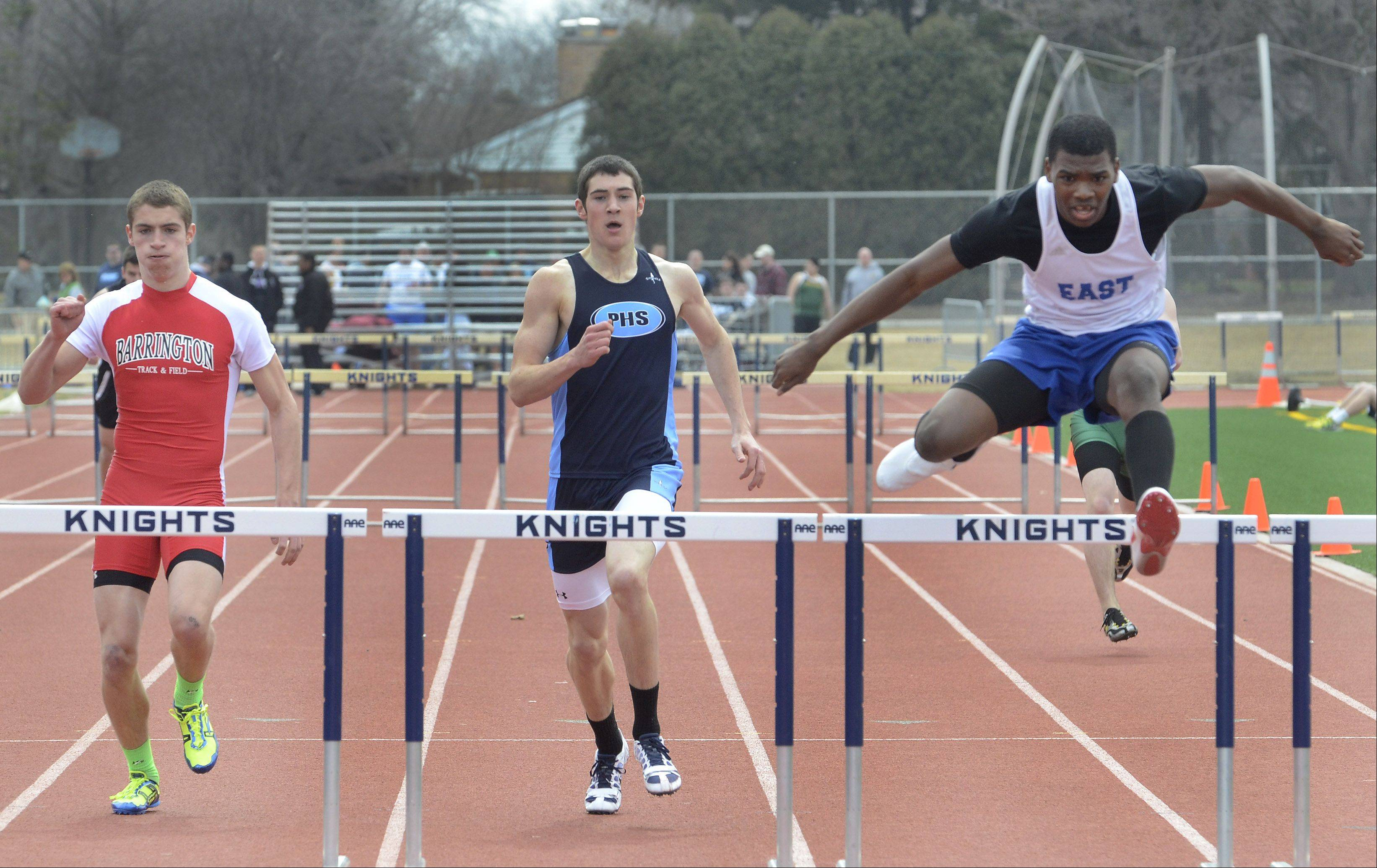 Jalen Lewis of Maine East, right, wins the fourth heat of the 300 intermediate hurdles, with Prospect's Dave Kendziera in second after stumbling, and Barrington's Jace Goetsch finishing third in the Prospect Relays on Saturday.