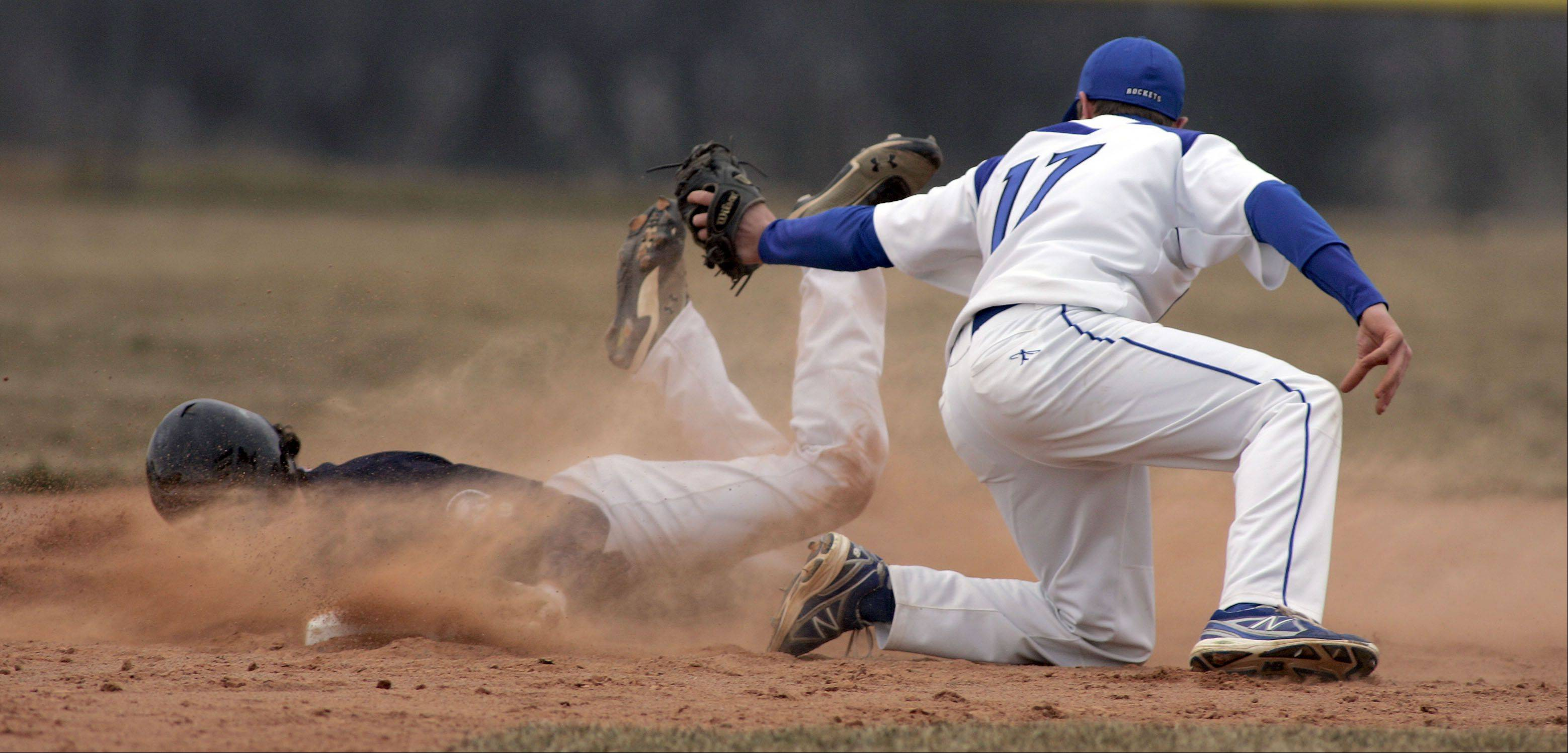 Burlington Central's Drew Wiss puts the tag on Cary-Grove's Dean Christakes as he gets a face full of dirt during Cary-Grove at Burlington Central baseball Saturday.