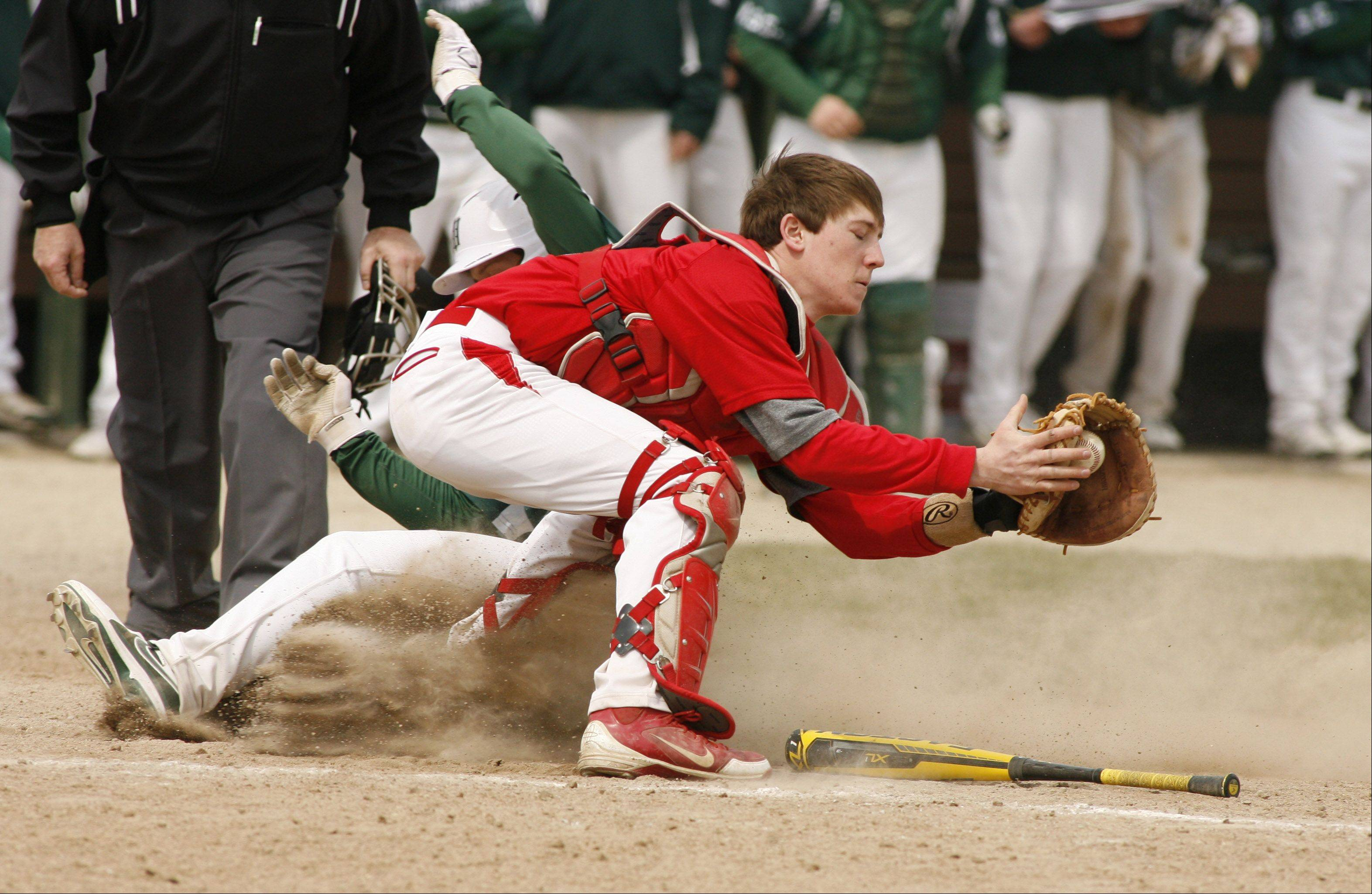 The Hilltoppers' Spencer Refer slides safely into home past catcher Tyler Ward to score the winning run, during Glenbard West's 6-5 win over Hinsdale Central.