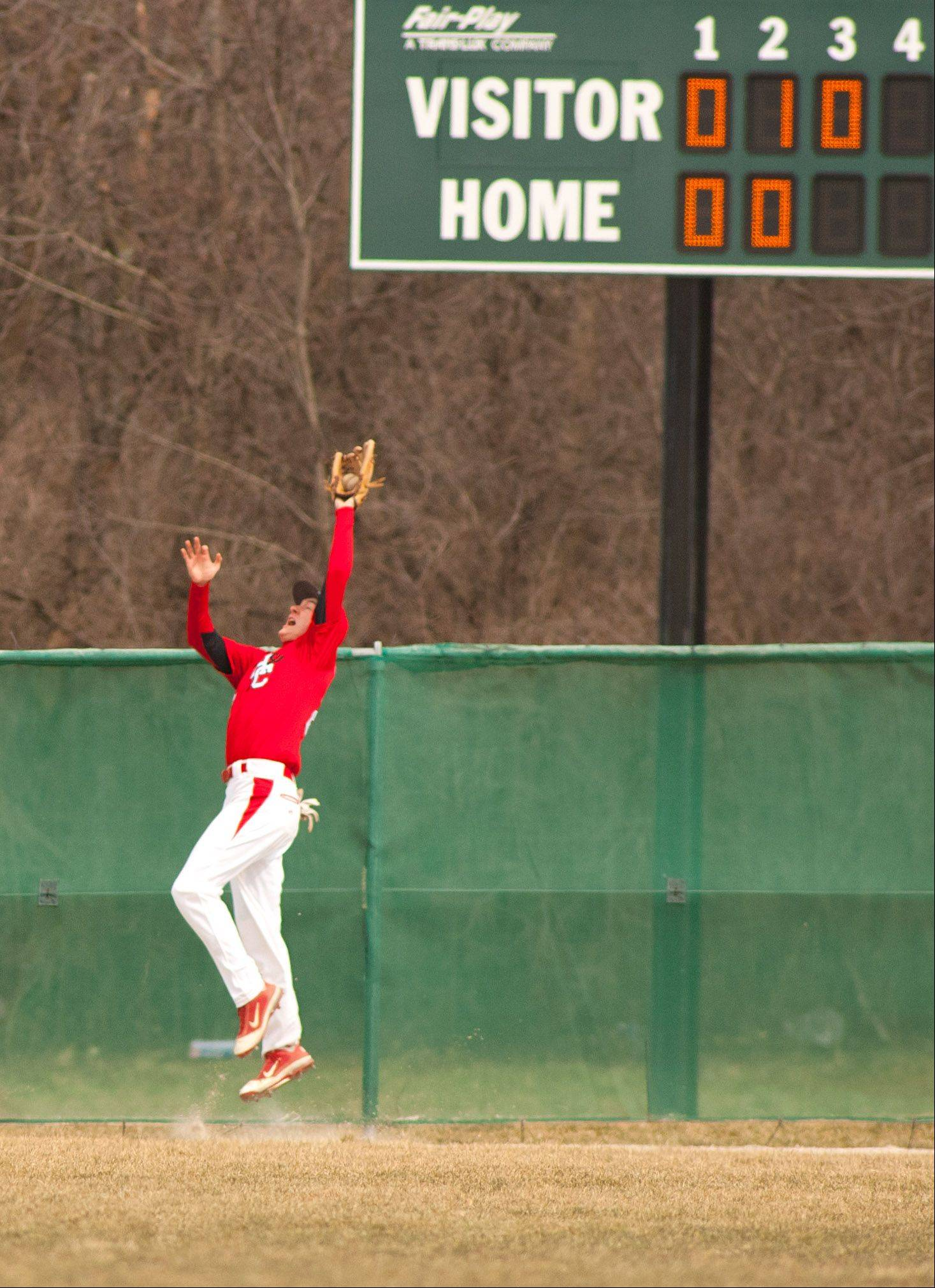 Hinsdale Central's Alec Hutcherson makes a catch at the fence against Glenbard West.