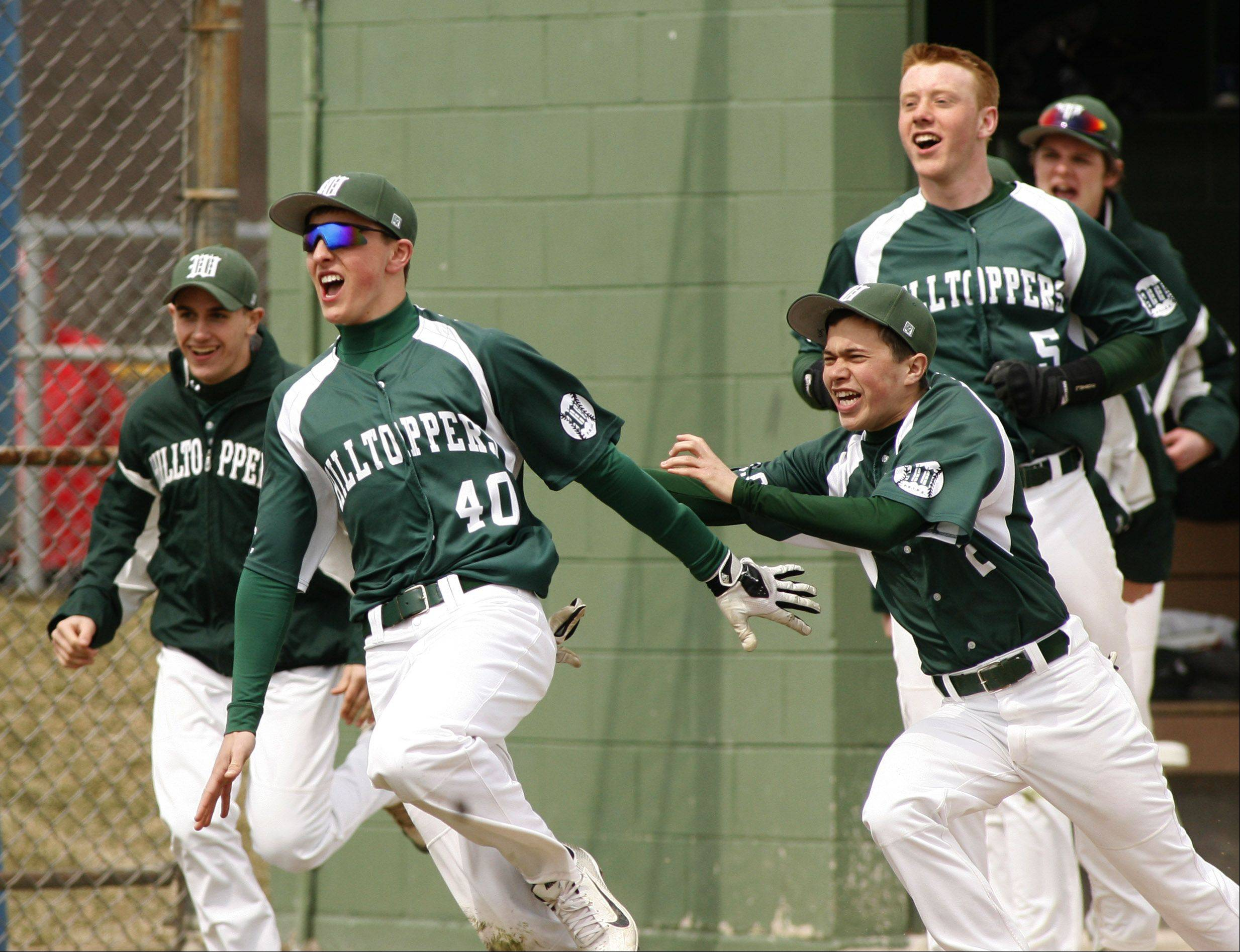 Luke Domask (40) leads the charge out of the dugout to celebrate Glenbard West's 6-5 win over Hinsdale Central.