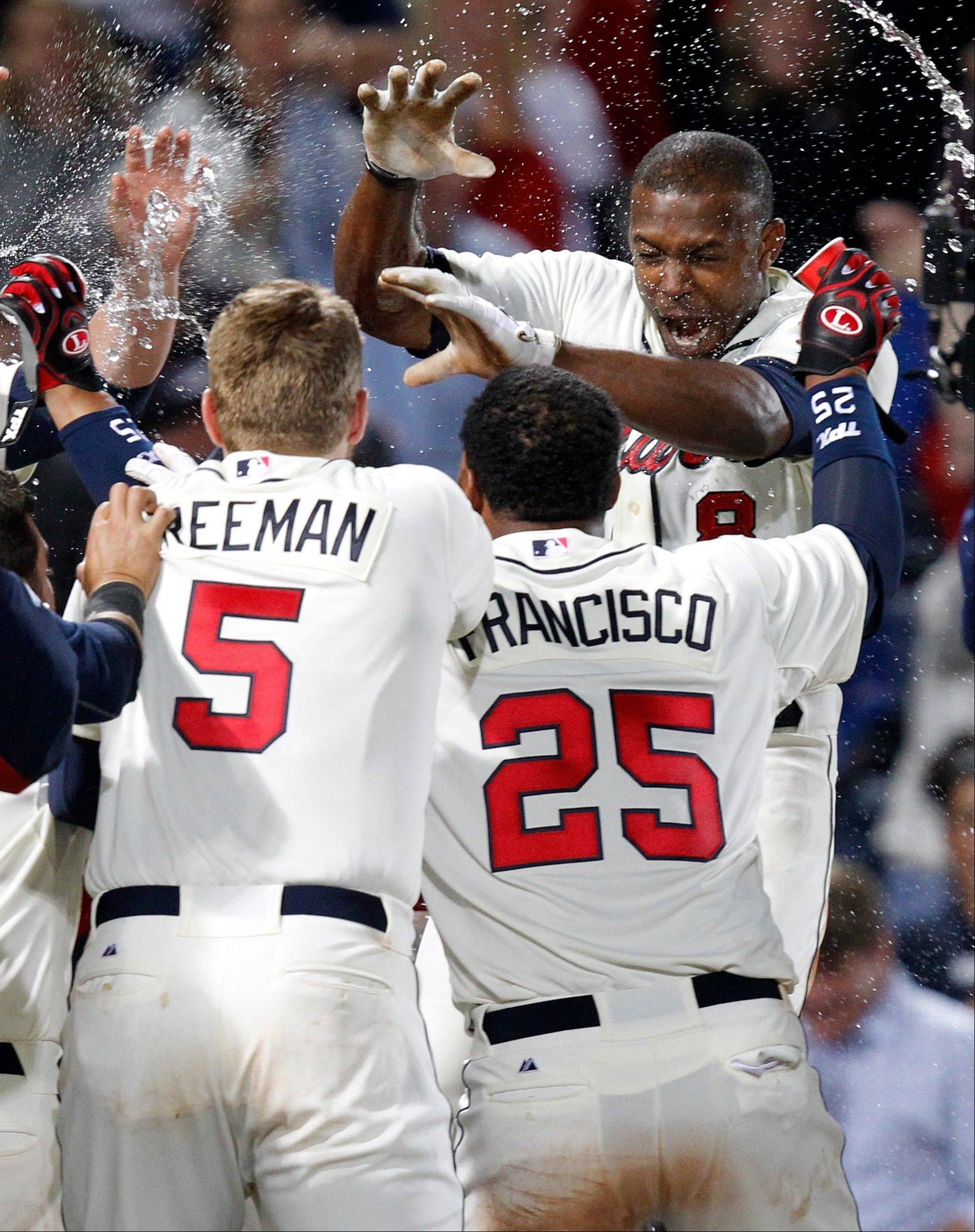 The Braves� Justin Upton, top right, is doused by teammates as he crosses home plate after hitting a walk-off home run in the ninth inning against Cubs reliever Carlos Marmol. Two batters earlier, Justin�s brother B.J. had tied the game with a home run.