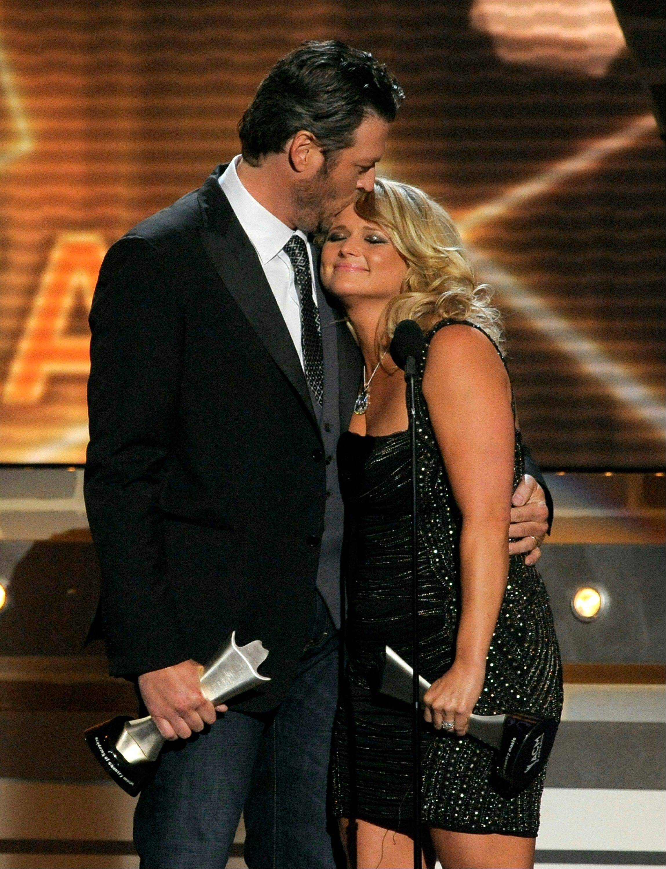 "Miranda Lambert, right, and Blake Shelton accept the award for song of the year for ""Over You"" Sunday night."
