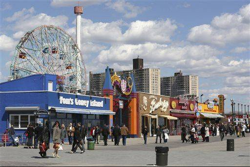 Visitors to New York's Coney Island walk on the boardwalk past the open businesses.