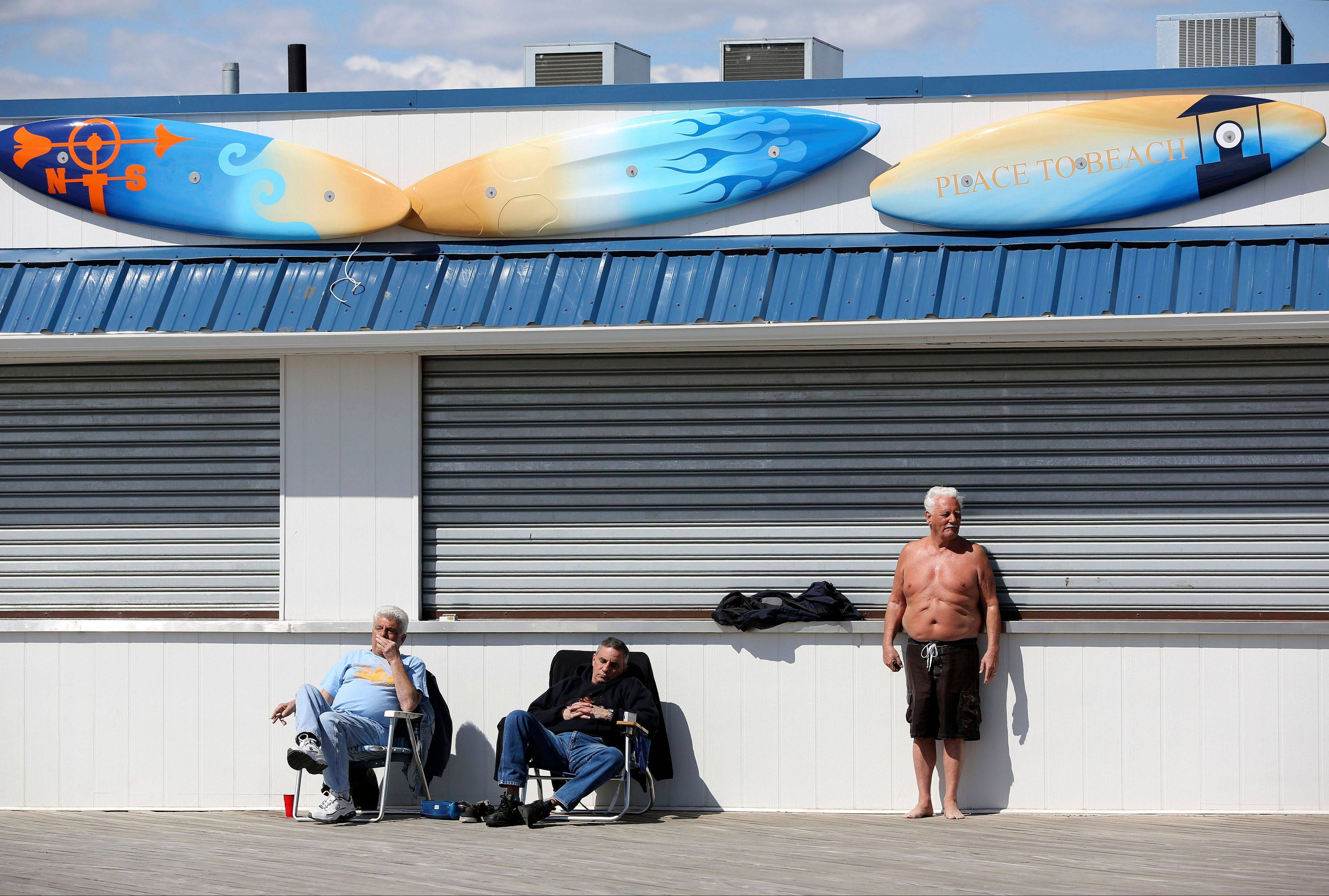 Men sunbathe in front of a closed business on the boardwalk of New York's Coney Island.