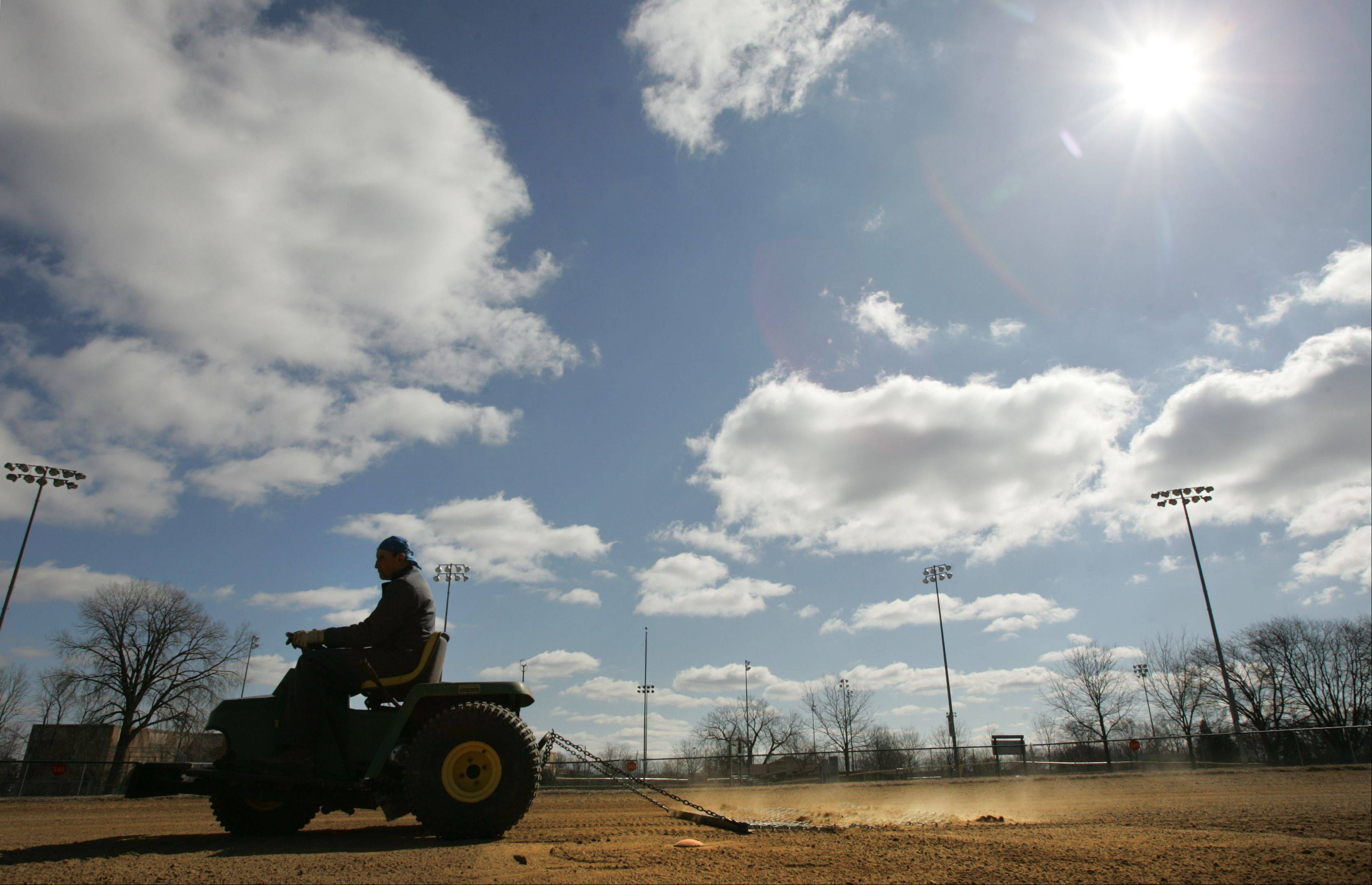 Elgin public works department employee Bill Rodriguez preps a ball diamond Monday morning in anticipation of a St. Edward Catholic High School baseball game later that day in Wing Park on Elgin's northwest side.