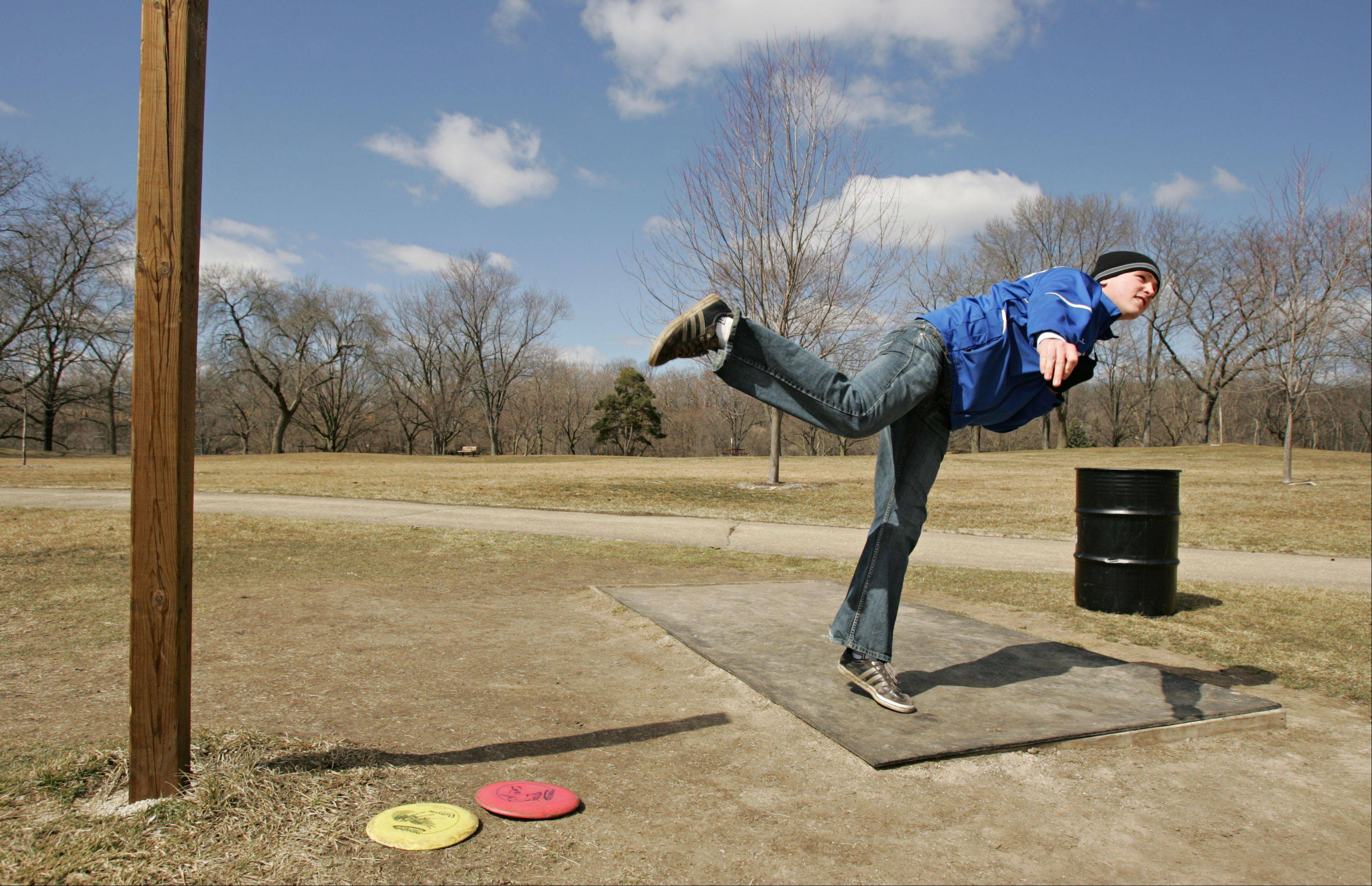 Jack Piotrowski, 18 of St. Charles, hurls his tee shot down the fairway in Wheeler Park Monday afternoon in Geneva while playing a round of disc golf. The Wheaton St. Francis senior had the day off from school, but had to play solo since his golfing buddies were attending classes Monday at other schools. Piotrowski said he took up disc golf after injuring his arm playing baseball.