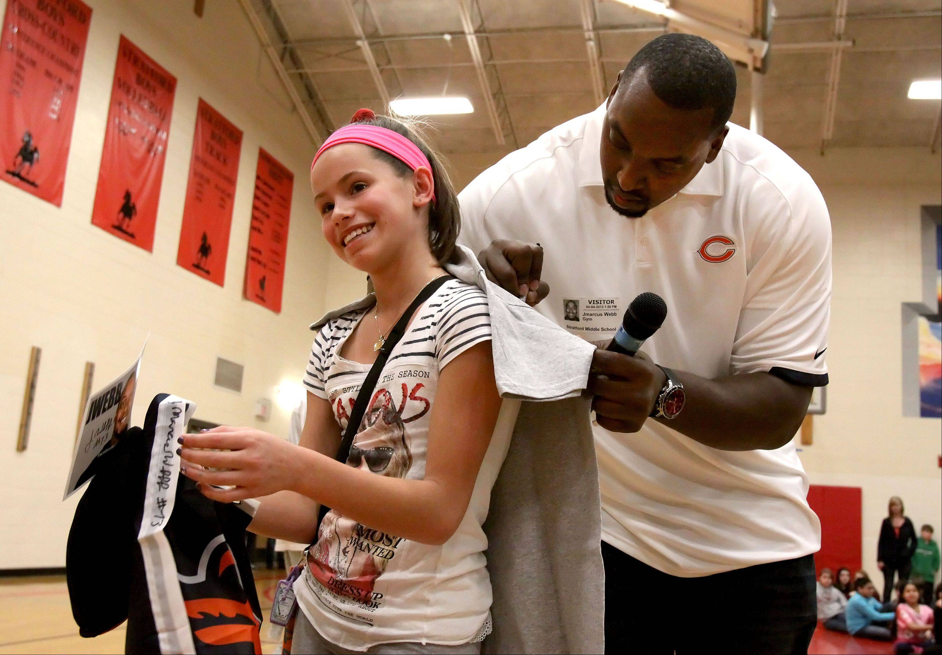 Giovanne Polina, 7th grade, gets an autograph from Chicago Bears offensive lineman J'Marcus Webb. She was the top fundraiser last year for Football for Heart. He appeared and talked about the importance of exercise and physical activity at Stratford Middle School in Bloomingdale Thursday.
