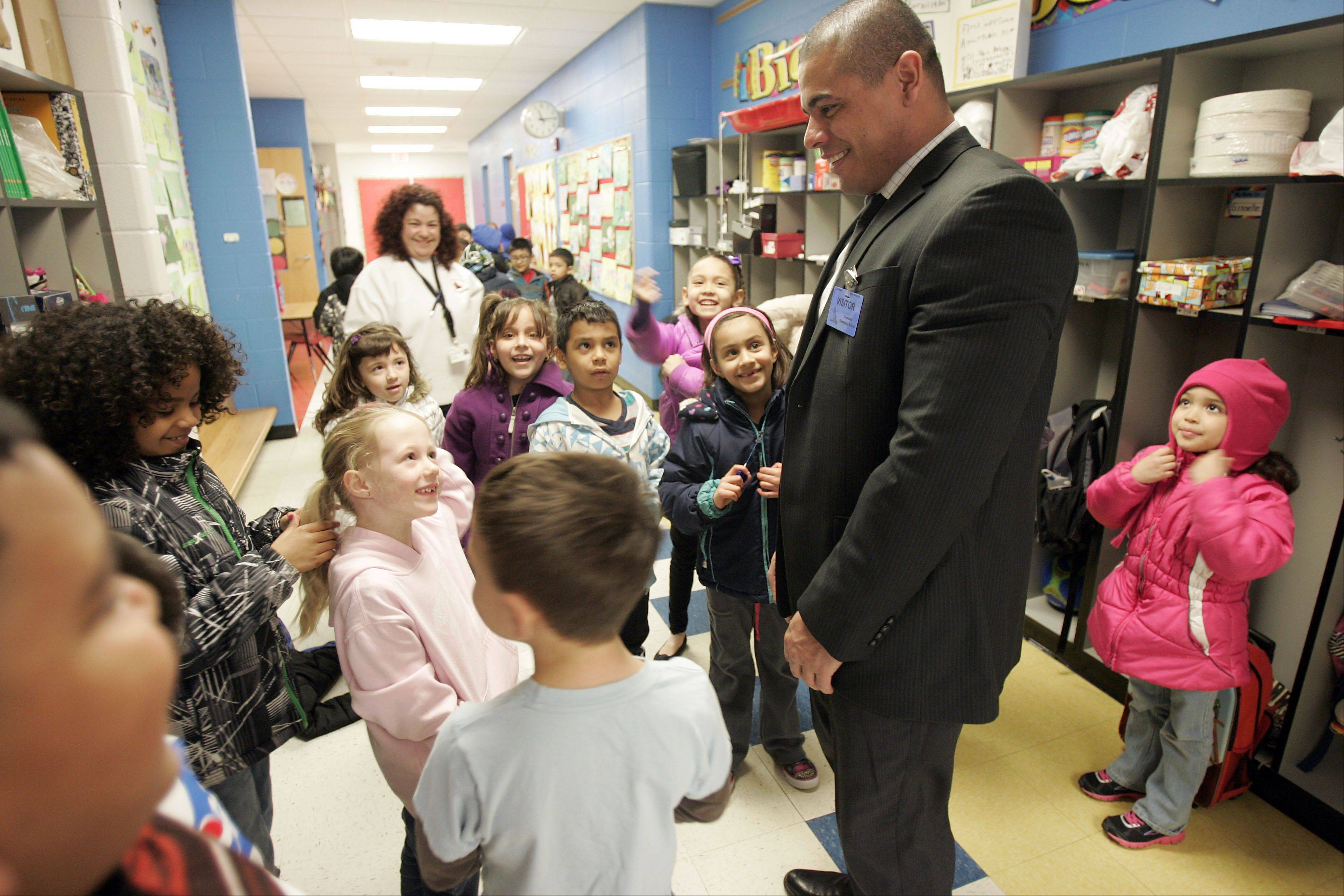 Resident Officer Eric Echevarria of the Elgin Police Department, jokes around with some of the students as he tours the halls of Creekside Elementary School in Elgin Friday serving as the principal for a day.