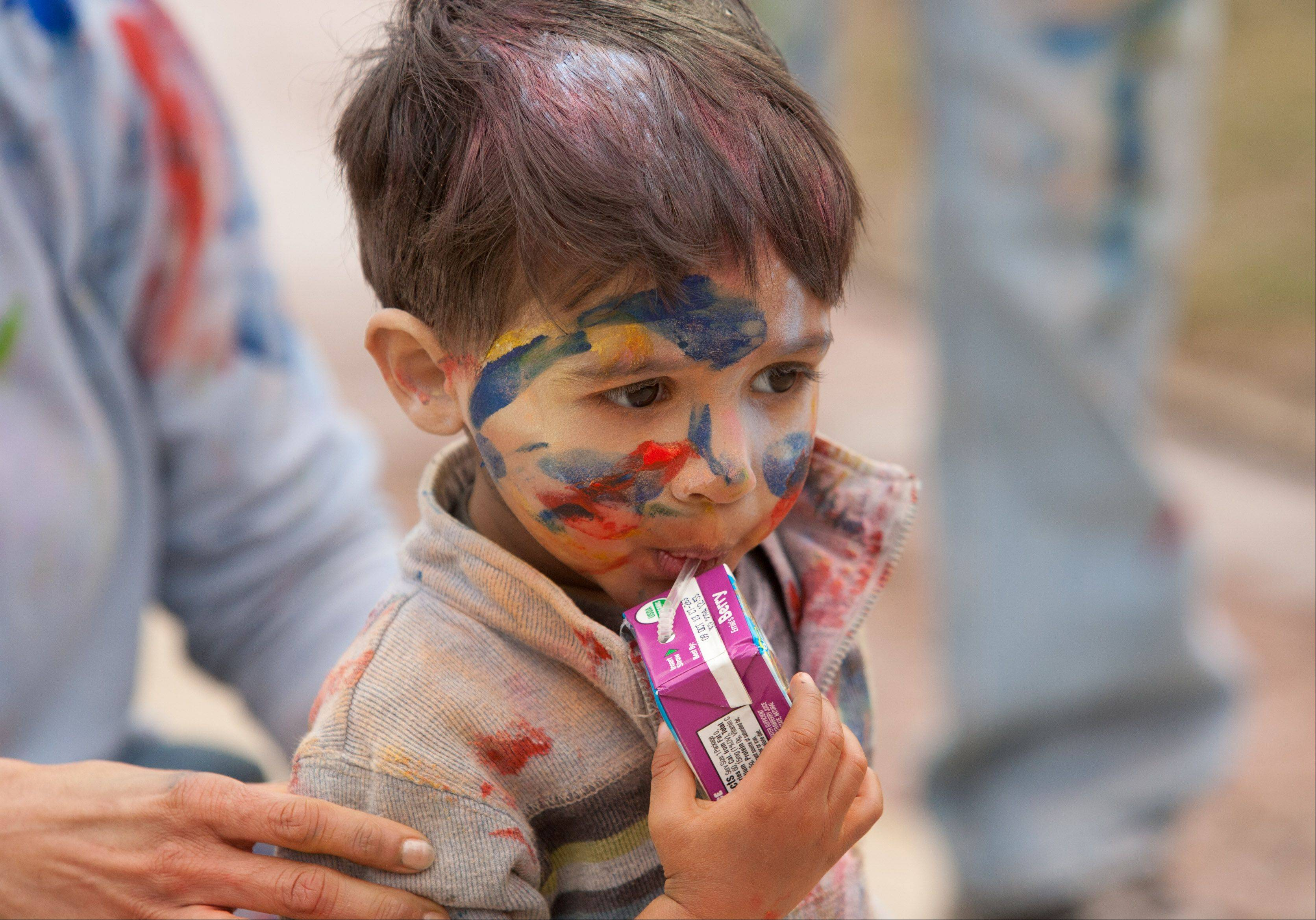 Lokesh Sulkar, 2, of West Chicago, pauses for a drink during the Simply Vedic Cultural Society's celebration of the Festival of Colors, that marks the passing of winter and arrival of spring.