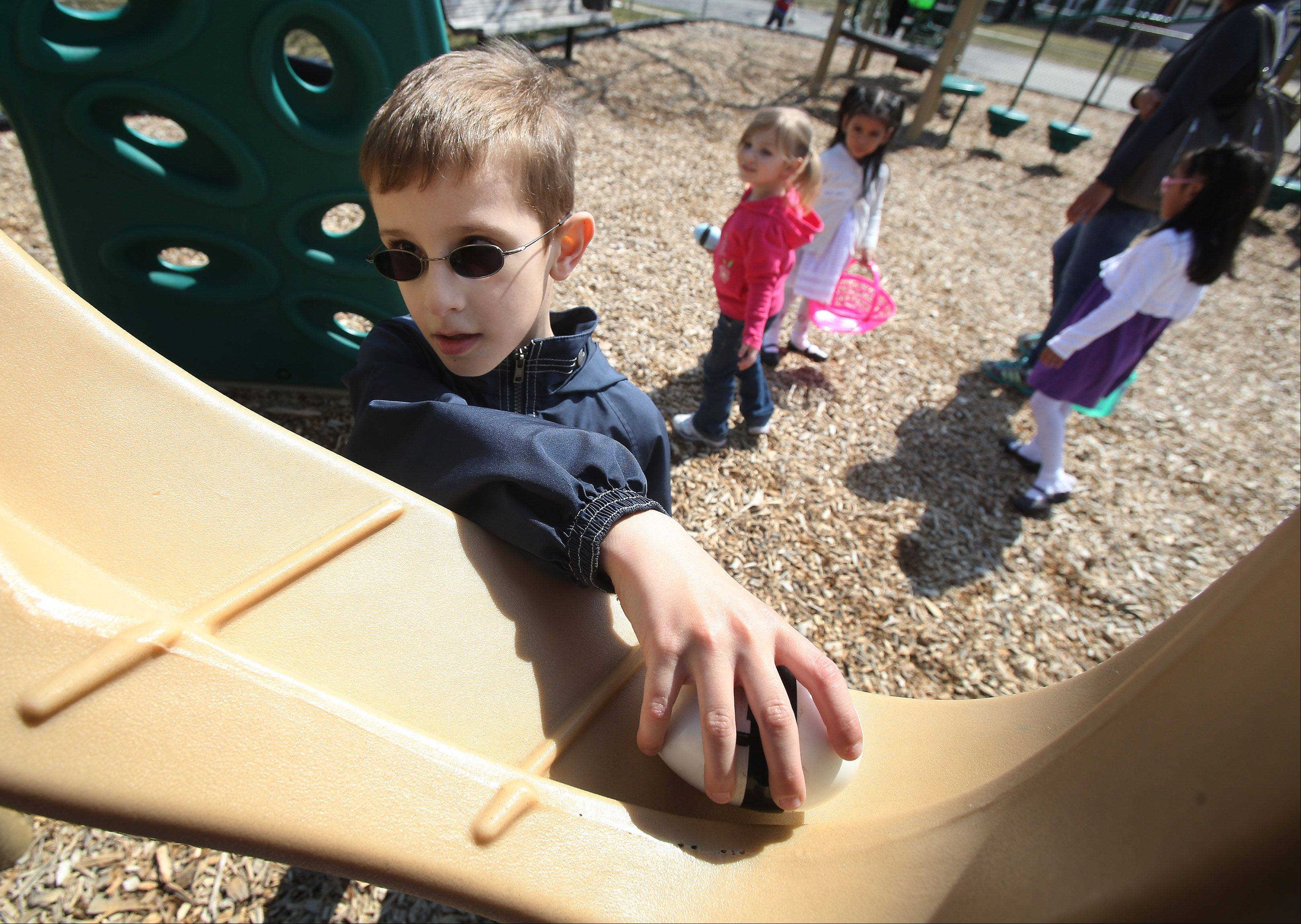 Angel Kaloyanov, 8, of Arlington Heights, finds a beeping egg in the playground during the Mount Prospect Lions Club Easter Egg Hunt Sunday at the Westbrook School at the Gillet Center. Visually and physically impaired children looked for beeping eggs to exchange for prizes.