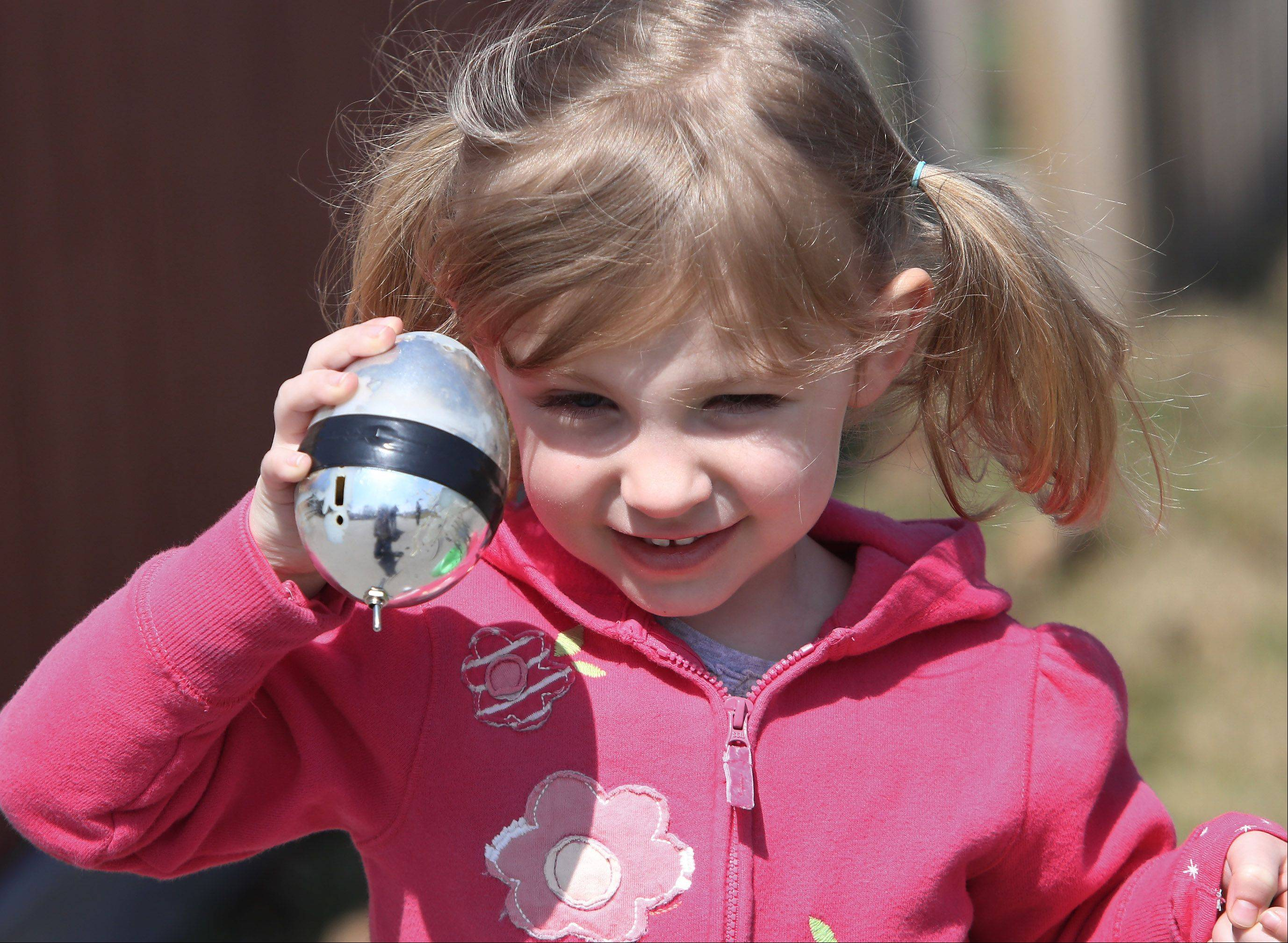 Kayla McCloskey, 3, of Arlington Heights, listens to a beeping egg she found during the Mount Prospect Lions Club Easter Egg Hunt Sunday at the Westbrook School at the Gillet Center. Visually and physically impaired children looked for beeping eggs to exchange for prizes.