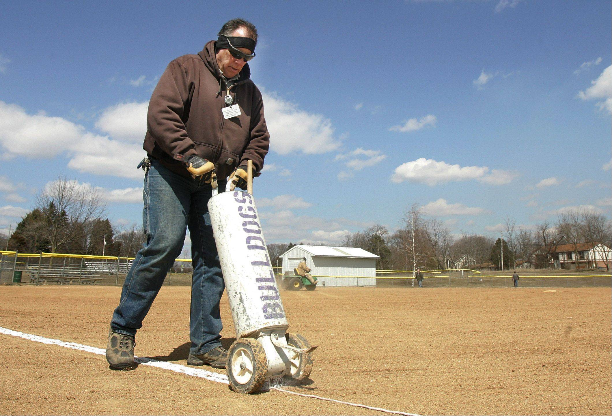 Grounds employee Tim Kleich, of Wauconda School District 118, lines the softball field in Cook Park Monday in preparation for the start of the high school softball season. The cold and snowy weather has delayed the use of the fields.