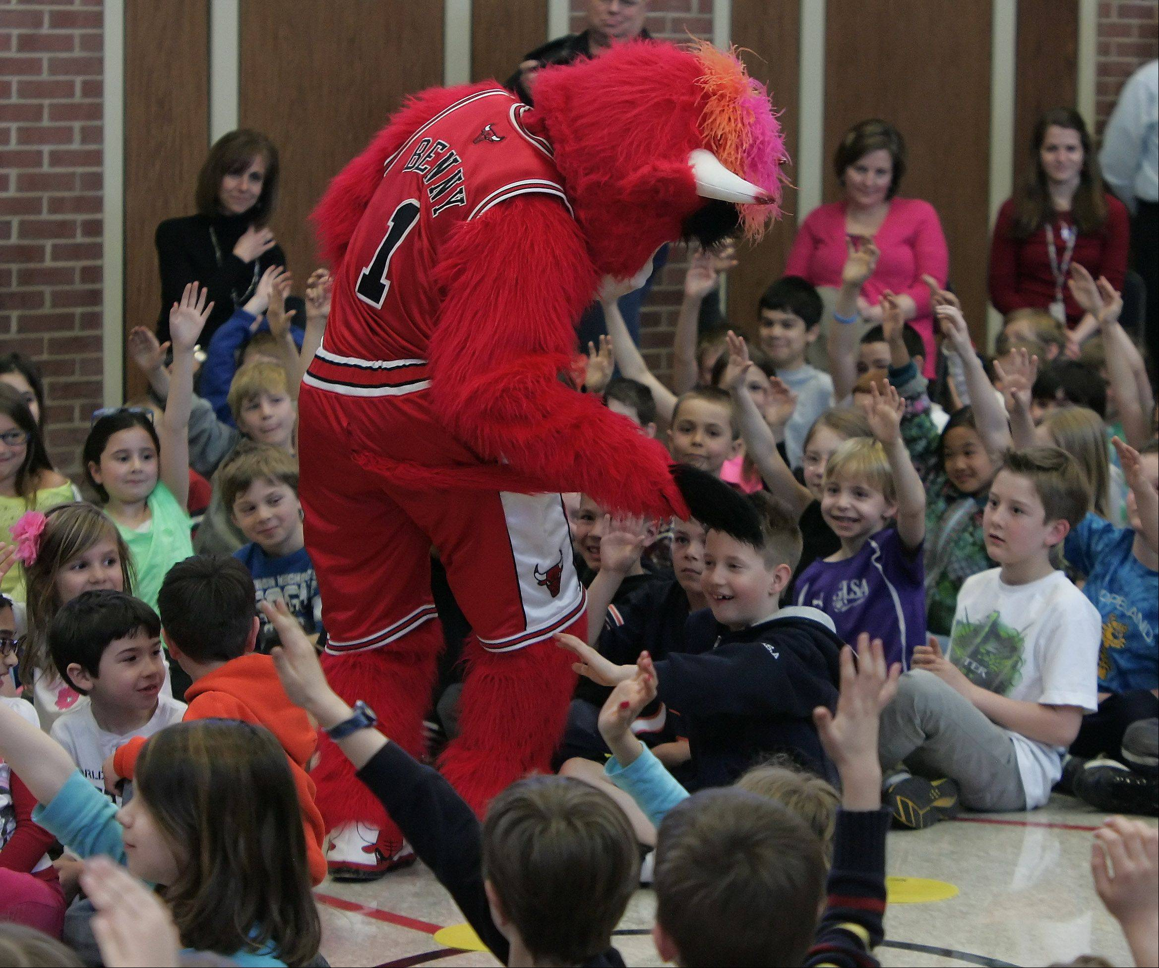 Benny the Bull wipes his tail over the face of second grader Zach Detlaff as he visits Copeland Manor School in Libertyville Tuesday. The visit was to teach about germs and proper hand washing techniques, and was sponsored by Advocate Condell Hospital and the Chicago Bulls.