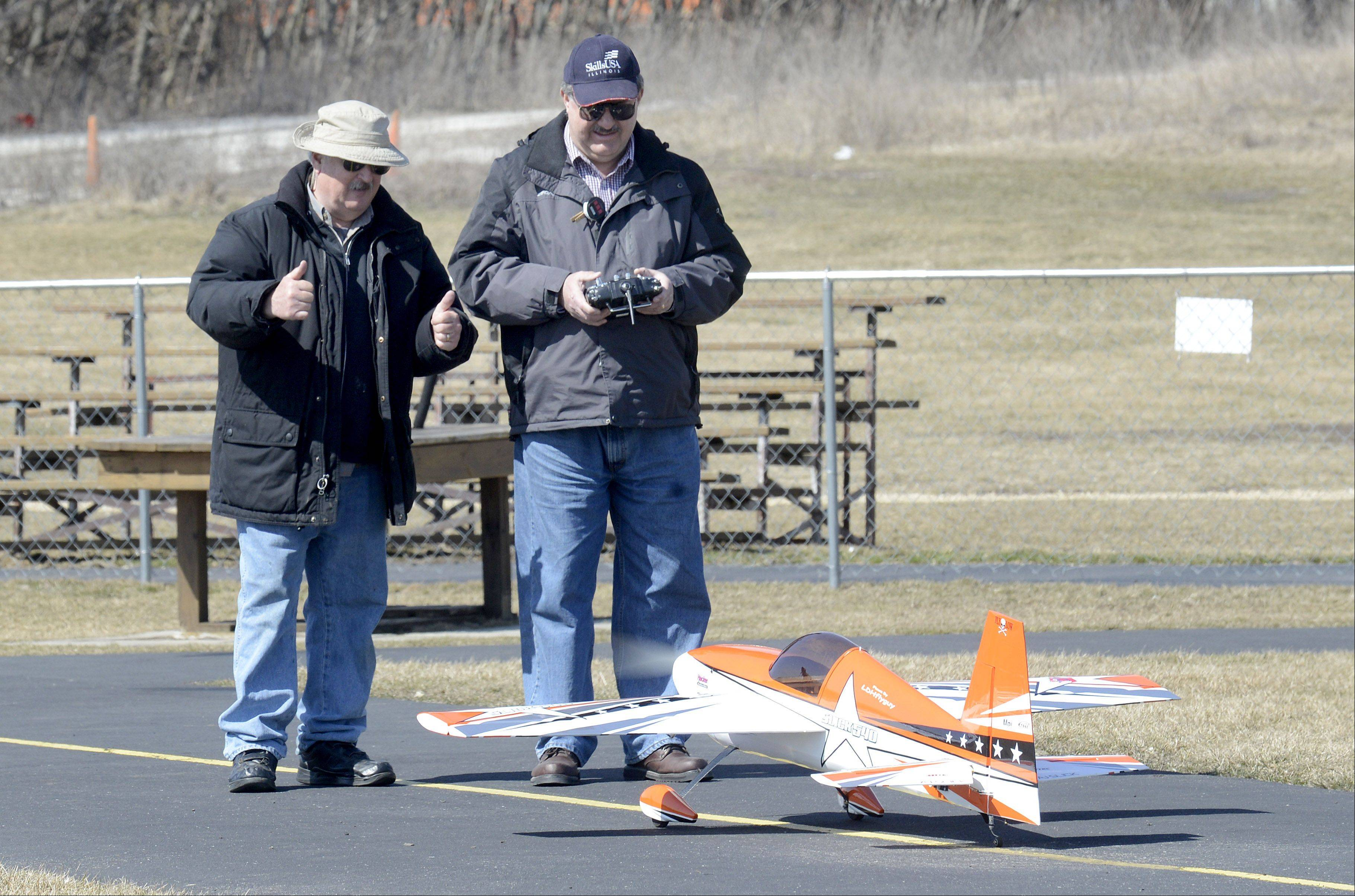 Tom Flint, of Geneva, gives Larry Huck, of Batavia, a thumbs up for his landing and taxiing while flying at the Fox Valley Aero Club's airstrip in St. Charles Wednesday. The aerobatic plane has a 72 inch wingspan. Flint was flying his planes since mid morning and Huck joined him about 2:30. Both men are members of the club and are at the airstrip flying as often as they can.