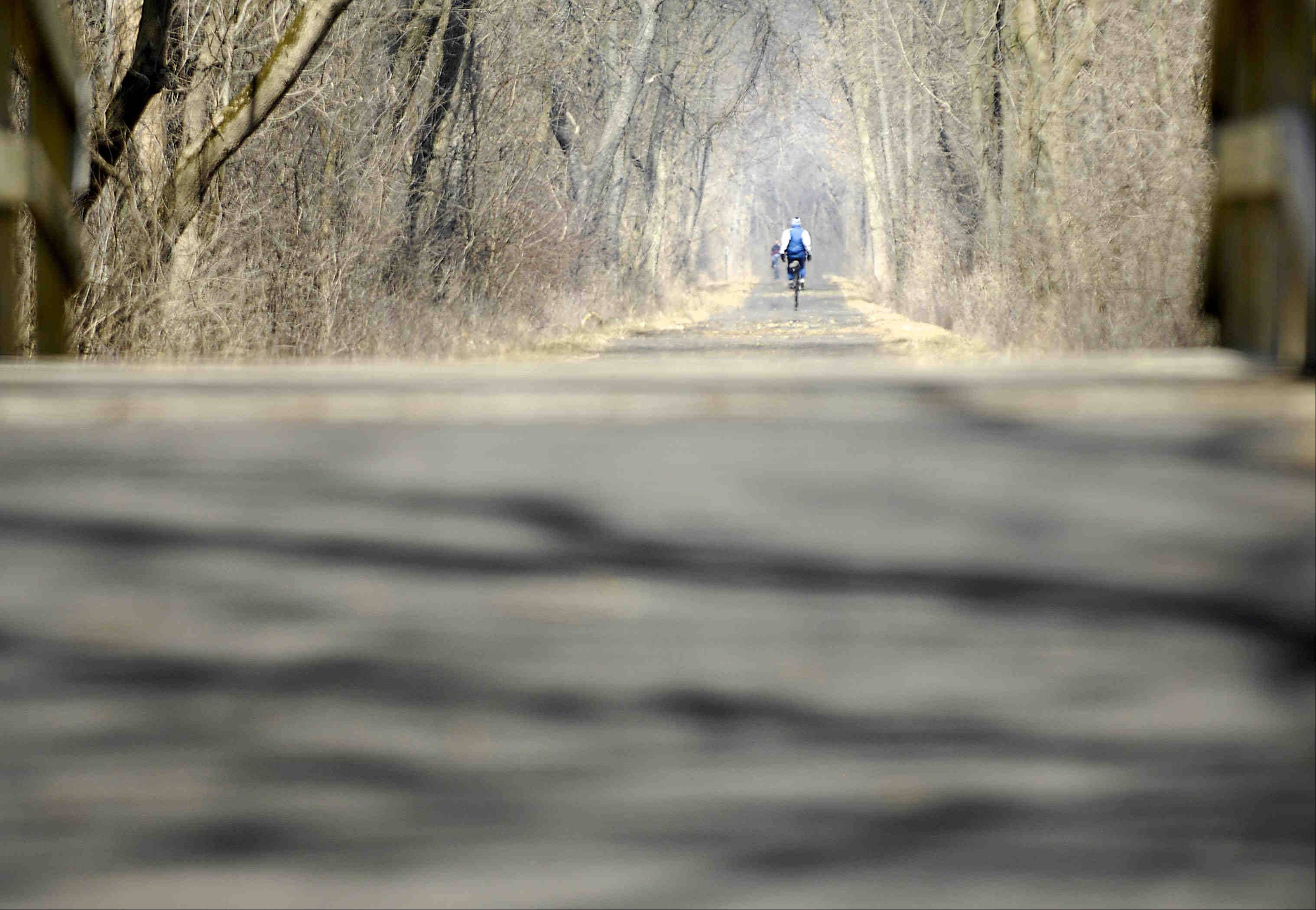 A rider pedals through smoke from a nearby controlled burn, in the afternoon sun on the Fox River Bike Path in Carpentersville Tuesday.