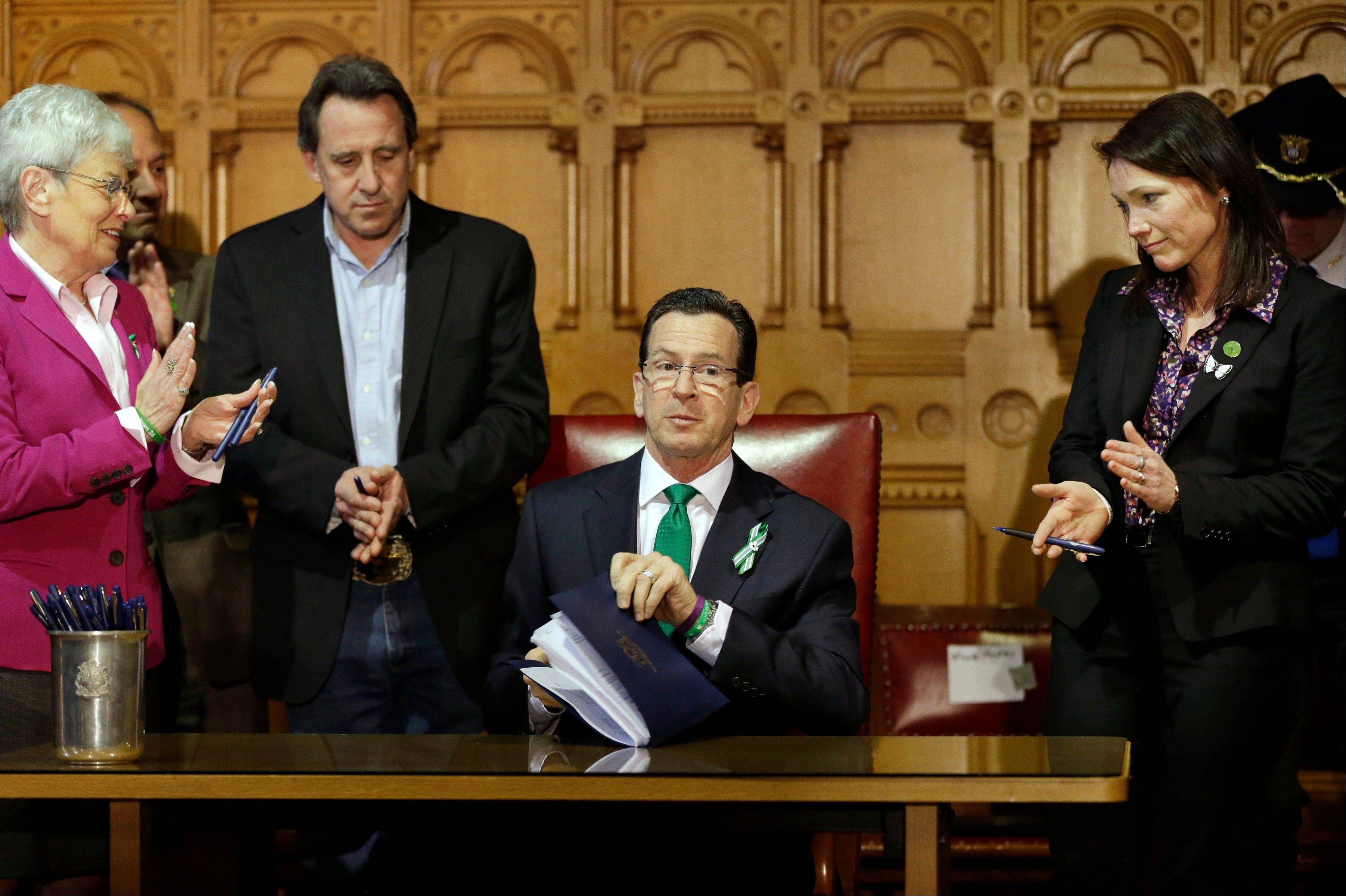 Connecticut Gov. Dannel P. Malloy, center, signs legislation that includes new restrictions on weapons and large capacity ammunition magazines at the Capitol in Hartford, Conn., Thursday.