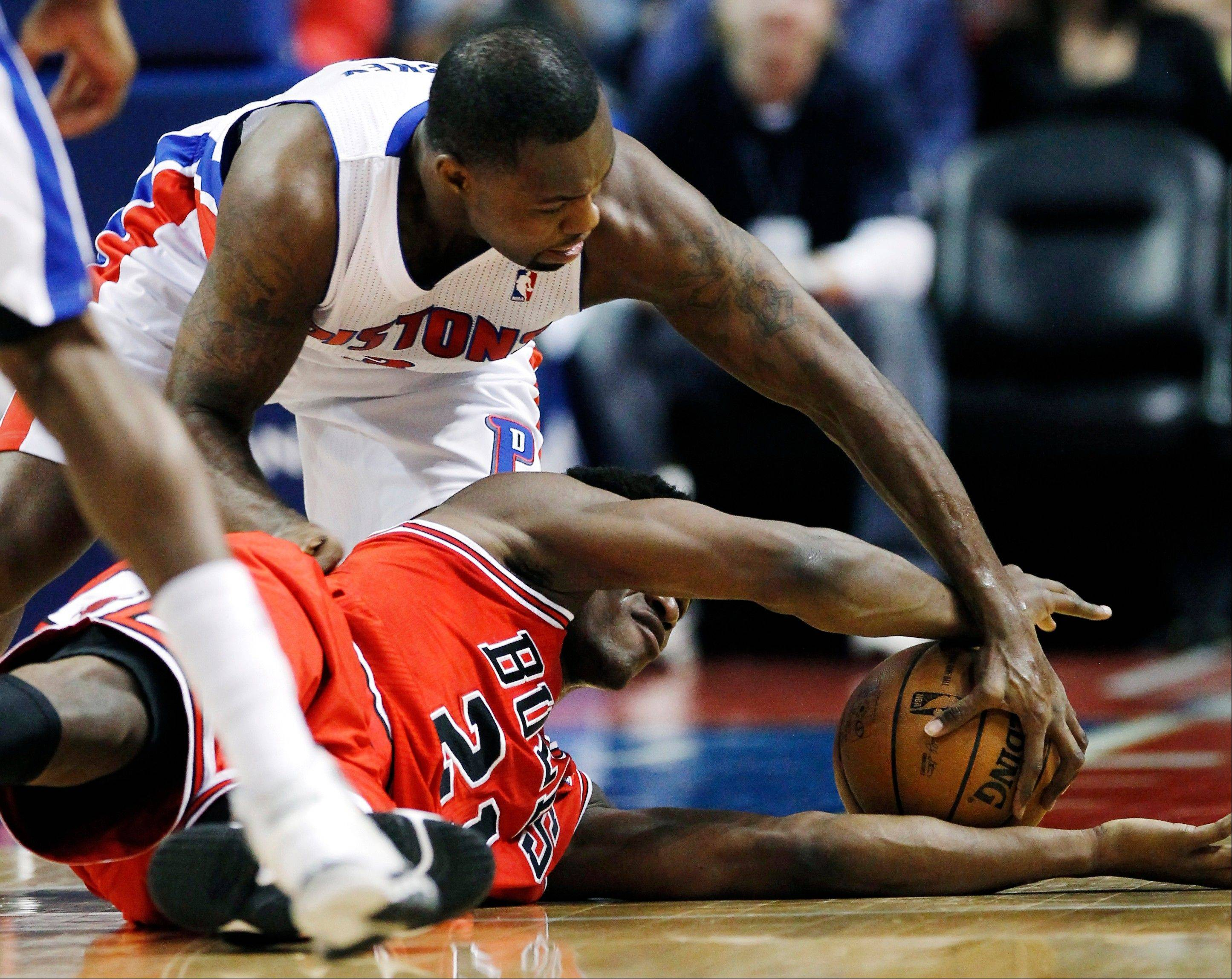 Detroit Pistons guard Rodney Stuckey, top, and Chicago Bulls guard Jimmy Butler (21) scramble for a loose ball in the first half of an NBA basketball game Sunday in Auburn Hills, Mich.