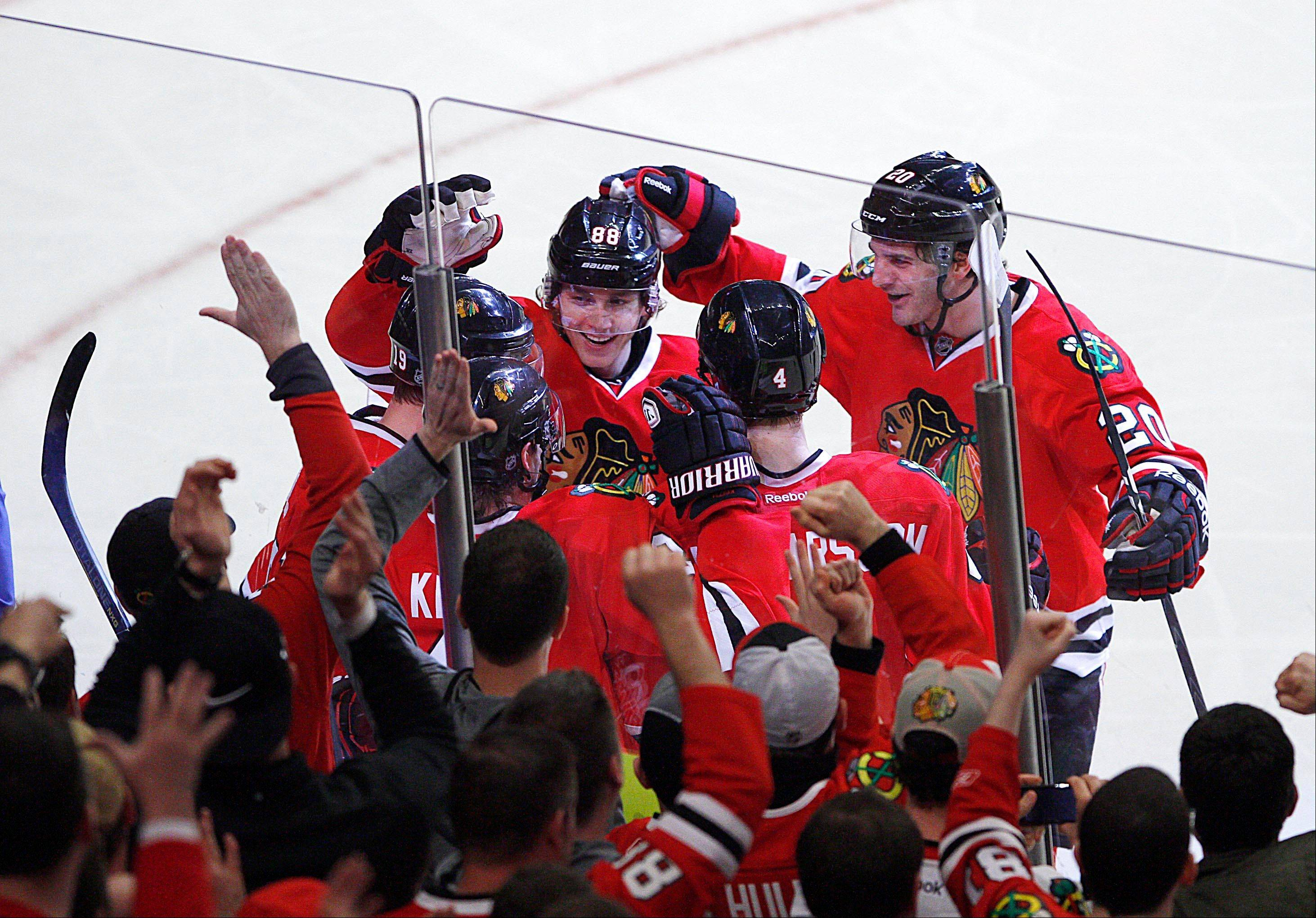 Chicago Blackhawks players including Patrick Kane, Brandon Saad, Duncan Keith and Niklas Hjalmarsson surround Jonathan Toews (lower left) after Toews scored the eventual game winner in the third period as the Hawks beat the Nashville Predators 5-3 in an NHL hockey game in Chicago on Sunday.
