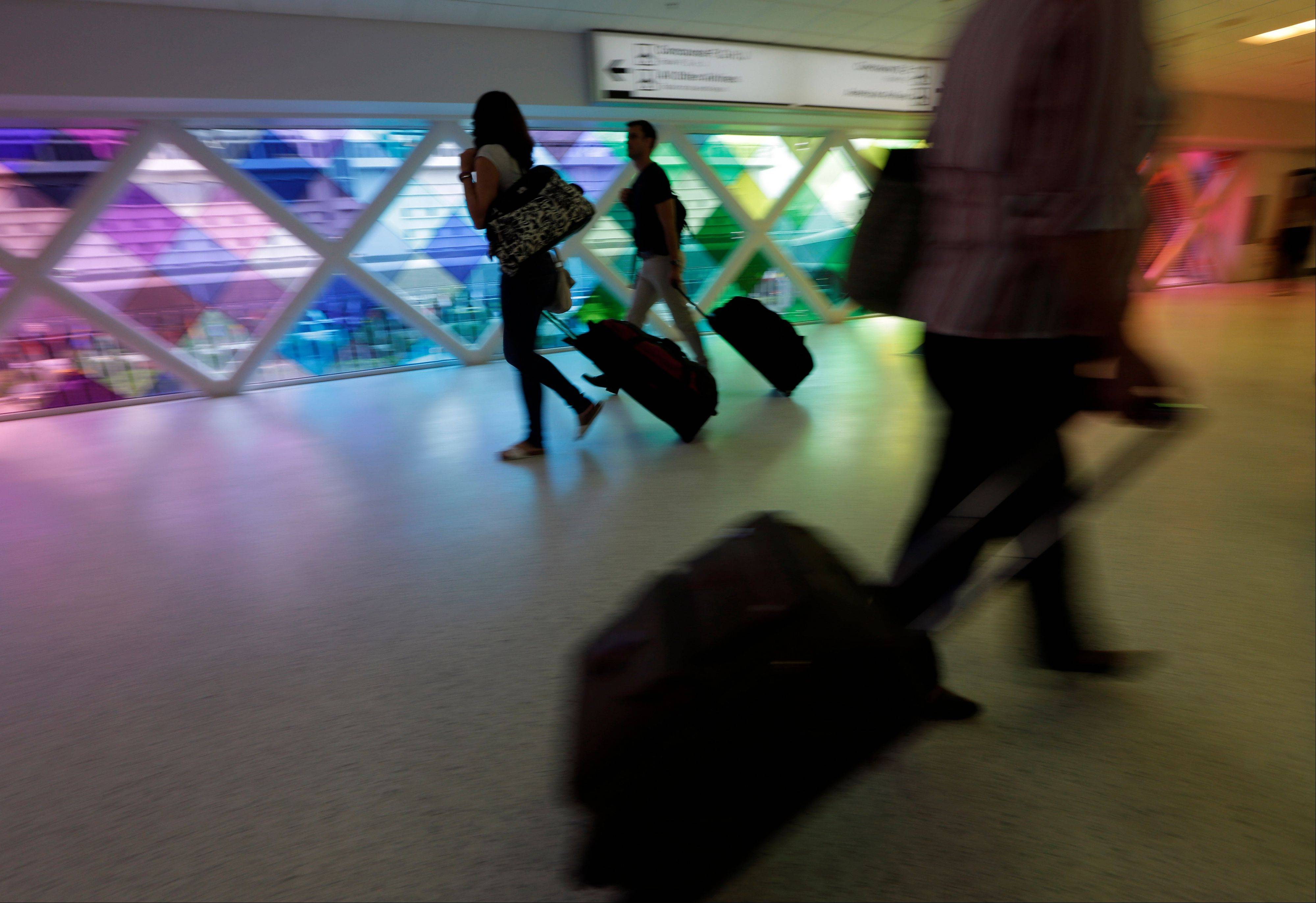Passengers travel through an airport in Miami. Private researchers, who have analyzed federal data on airline performance, say in a report that consumer complaints to the Department of Transportation surged by one-fifth last year even though other measures such as on-time arrivals and mishandled baggage show airlines are doing a better job.