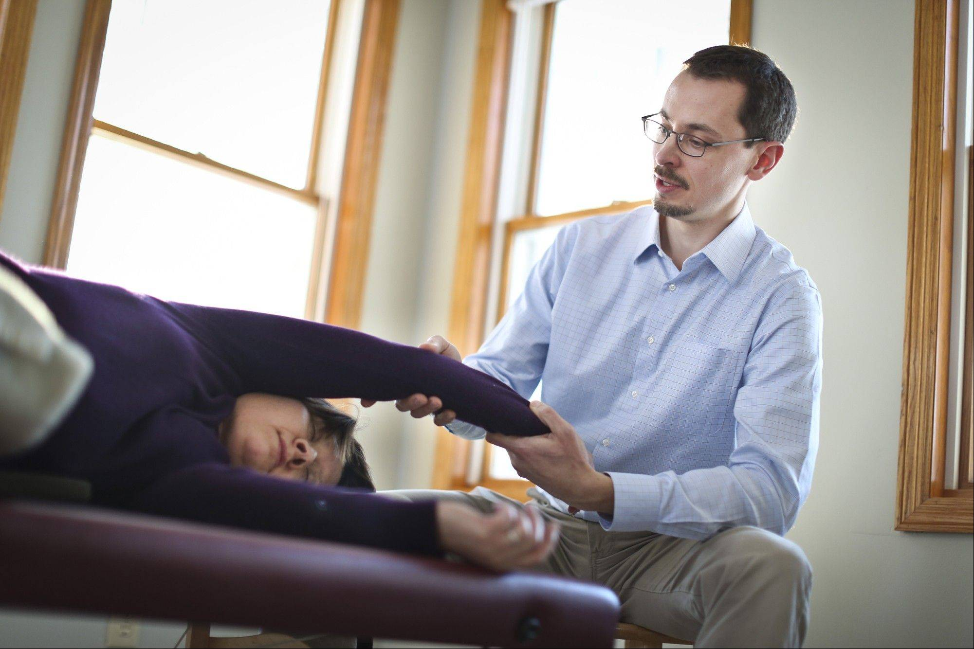 Feldenkrais practitioner Nick Strauss-Klein works with client Kathy Combs at his home.