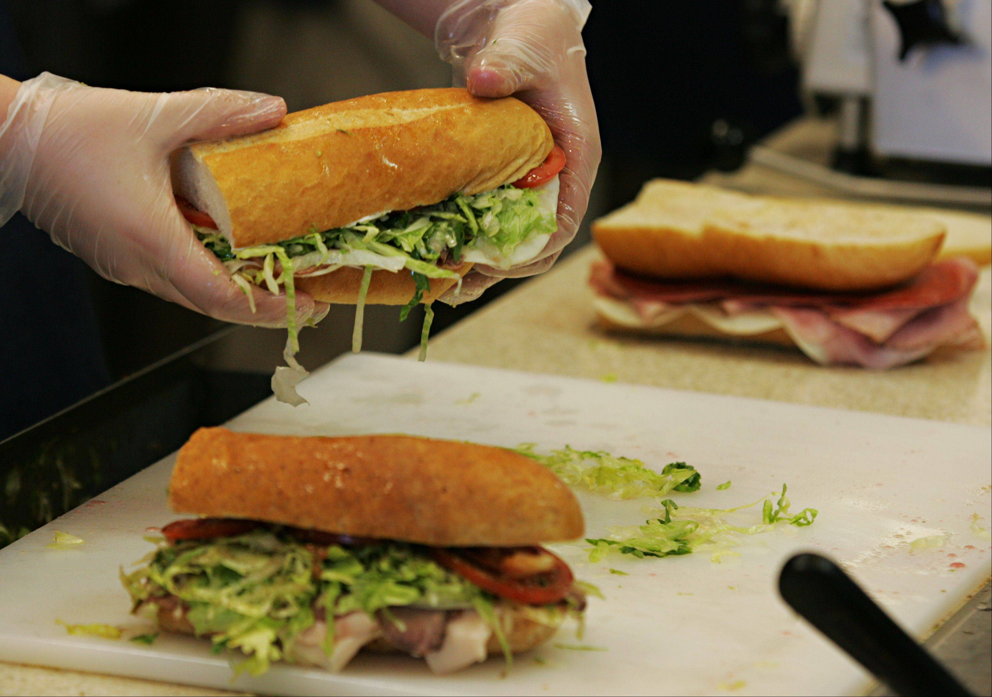 Jersey Mike�s Subs employee Matt Stickrod puts a sandwich together on the first day of business for the new location in South Elgin.