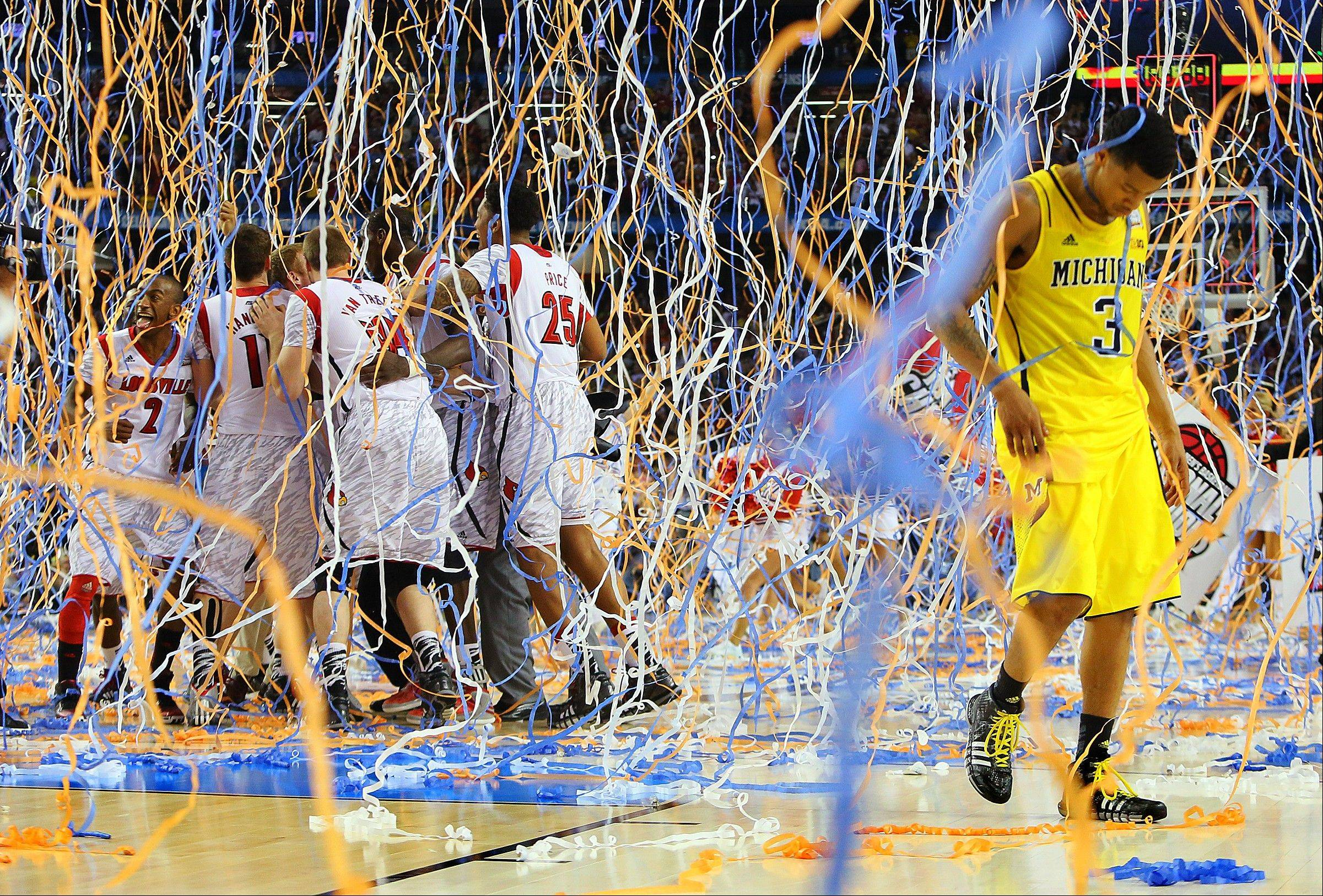 Michigan guard Trey Burke (3) walks off the court as confetti falls on Louisville players, including Russ Smith (2), Luke Hancock (11), Stephan Van Treese (44) and Zach Price (25), after the NCAA Final Four tournament college basketball championship game, Monday in Atlanta. Louisville won 82-76.
