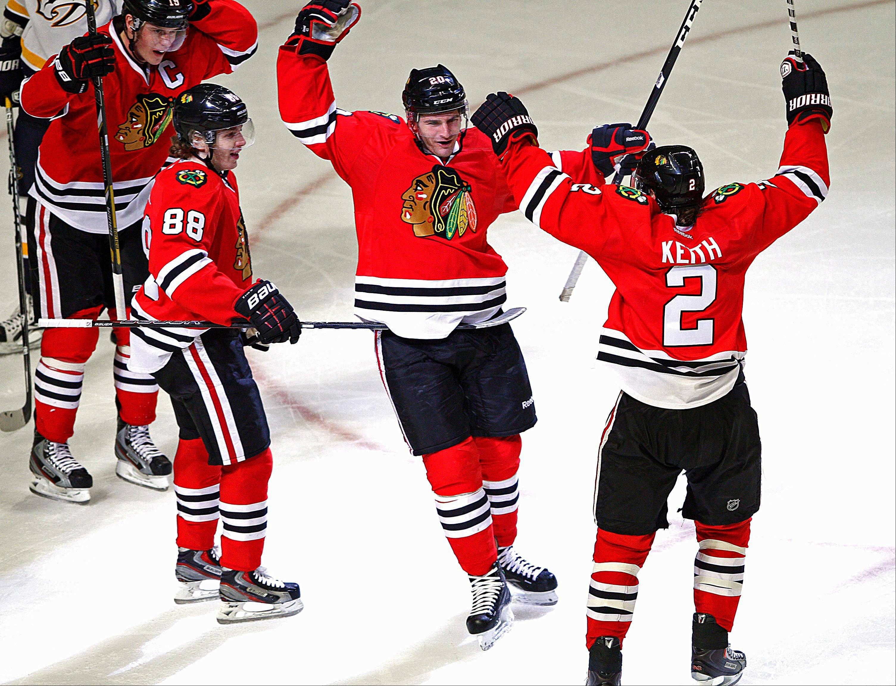Brandon Saad celebrates with Blackhawks teammates Duncan Keith and Patrick Kane after he scored in the third period against the Nashville Predators on Sunday. The Hawks have clinched a playoff spot and can no focus on securing home-ice advantage in the Western Conference.