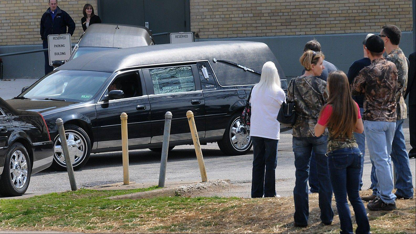 "A hearse leaves the Municipal Auditorium in Charleston, W.Va. after a joint funeral for ""Buckwild"" star Shain Gandee and his uncle David Gandee Sunday afternoon. Gandee, his 48-year-old uncle, David Gandee, and 27-year-old friend Donald Robert Myers were found dead April 1 in a sport utility vehicle that was partially submerged in a deep mud pit near Sissonville."