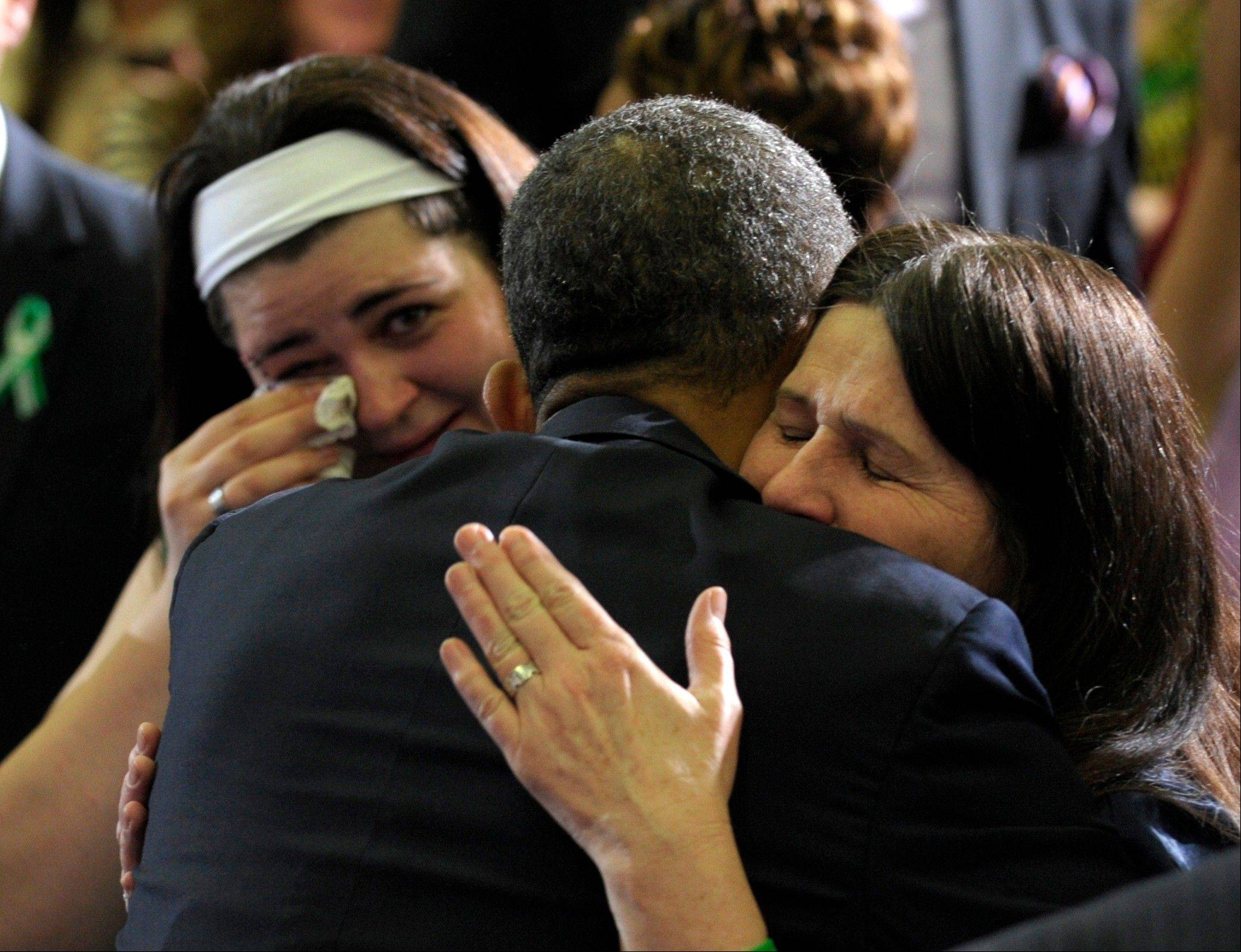 President Barack Obama hugs Newtown family members after speaking at the University of Hartford in Hartford, Conn., Monday. Obama said lawmakers have an obligation to the children killed and other victims of gun violence to act on his proposals.