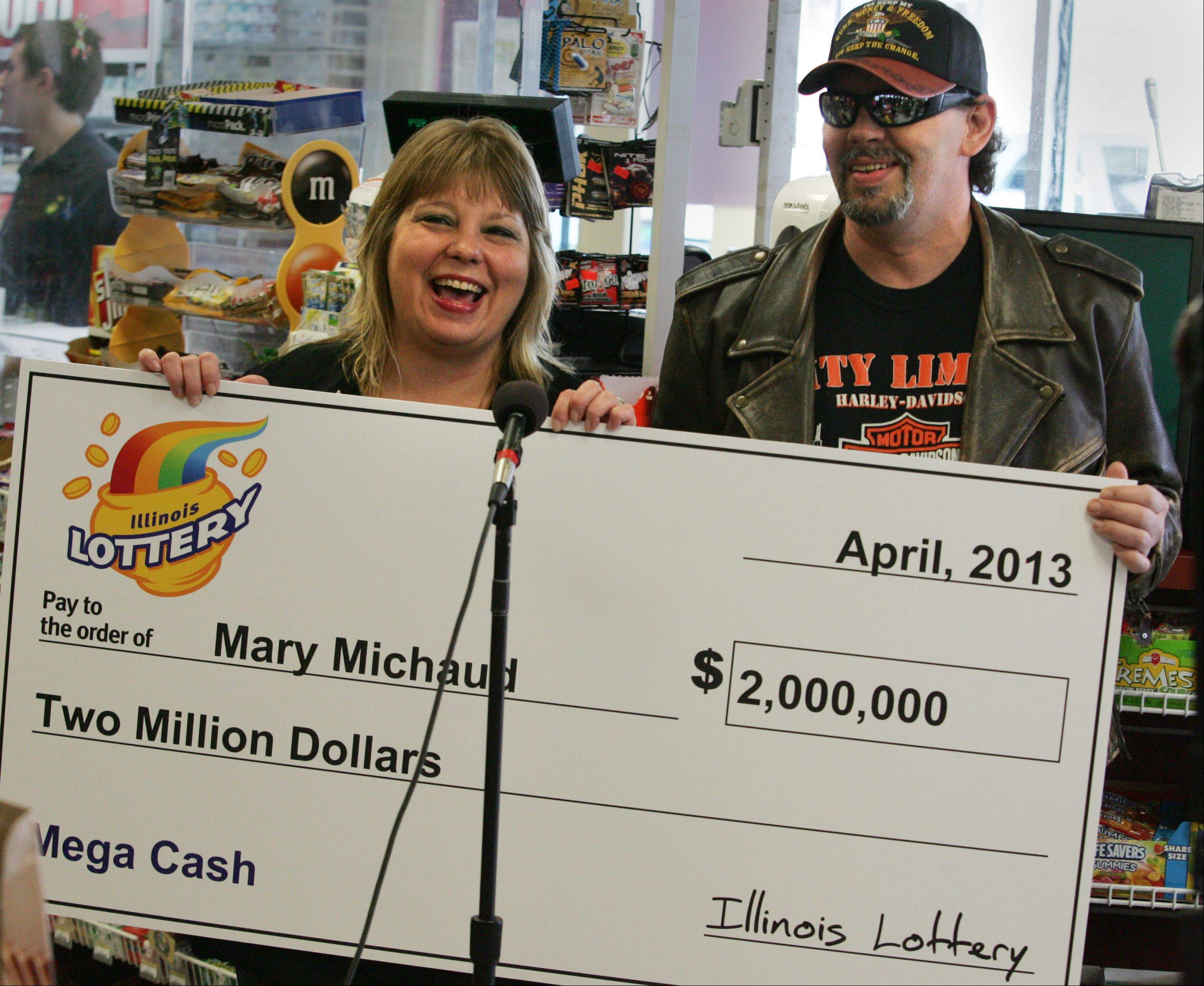 "Mary Michaud accepts a ceremonial check for $2 million along with her husband, Gil, during a presentation Monday at a BP store in Elgin where she had purchased the winning ticket on Good Friday. The Elgin couple say they will invest their money wisely, but splurge on a Harley-Davidson for Gil. ""I've got it on hold,"" he said. See our video of the couple at dailyherald.com."