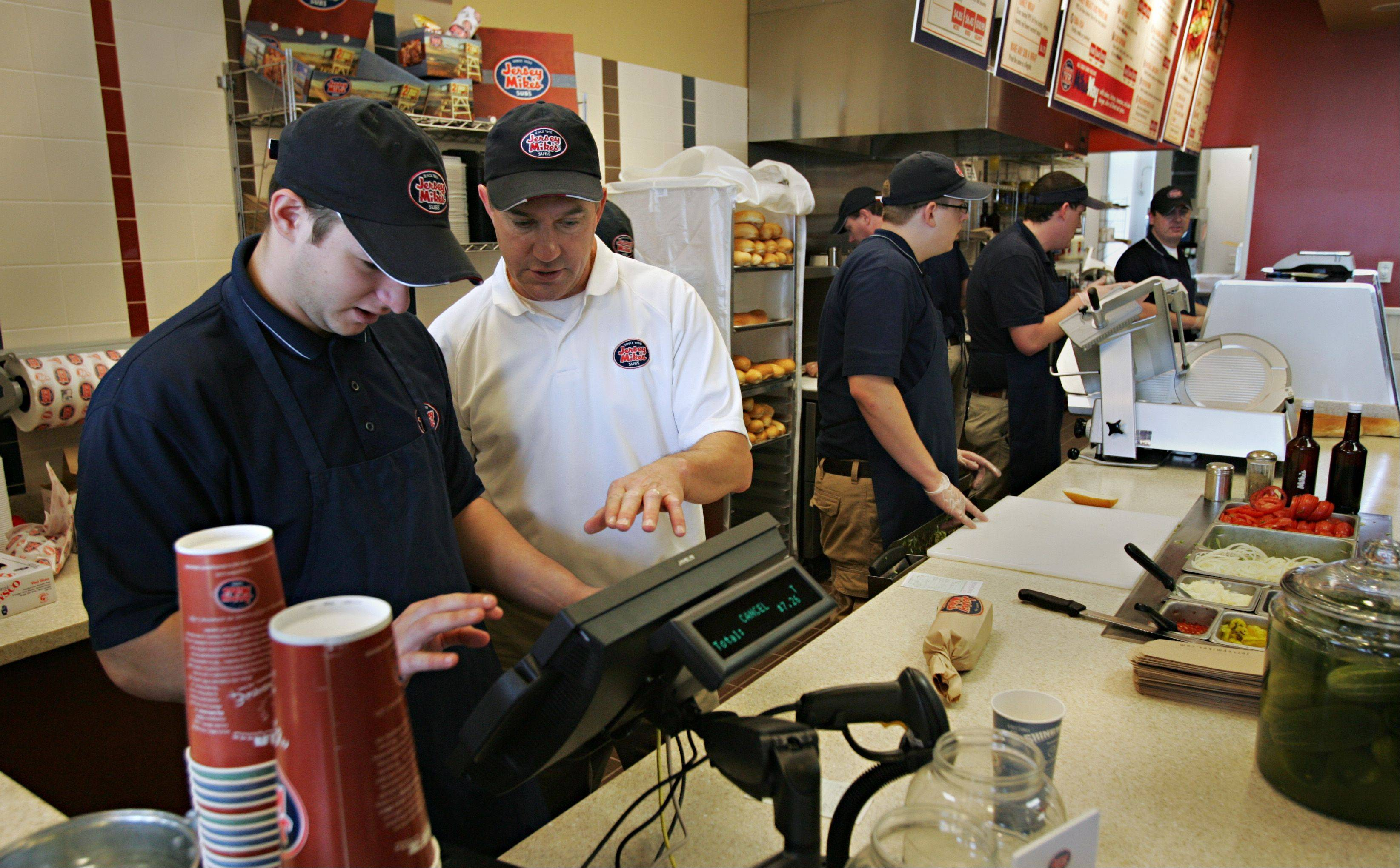Jersey Mike's Subs franchisee Jim Shipman works with new employee Zach Richman in South Elgin. In its first week in business, the restaurant raised funds for South Elgin and St. Charles North high schools.