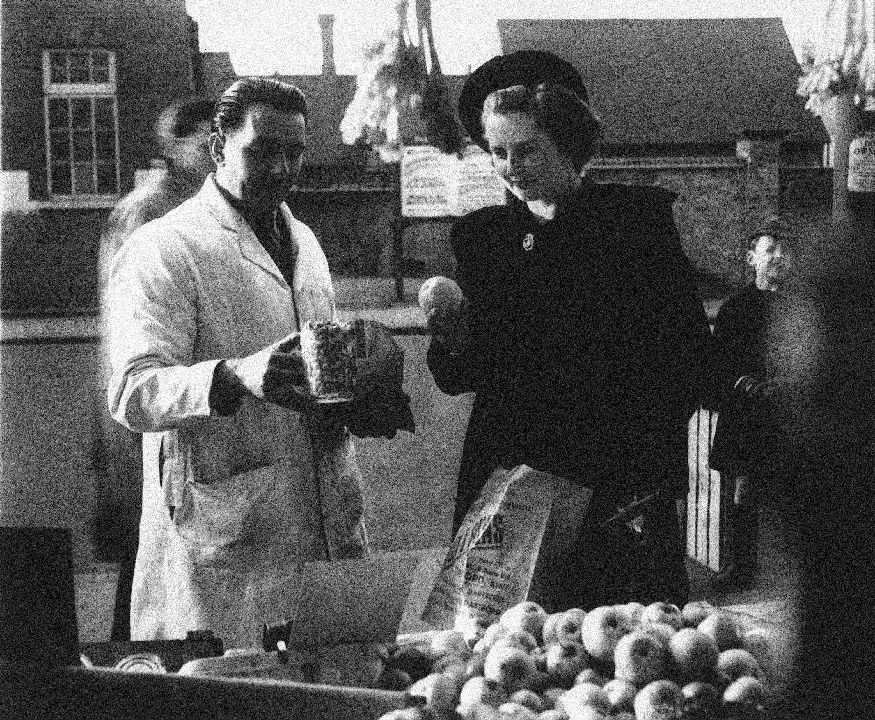 Youngest election candidate, conservative, Margaret Roberts (later Thatcher) buys a pint of peanuts and studies the quality of a lemon while shopping in Dartford, Kent, England in 1950, where she is standing as Tory M.P. Thatchers former spokesman, Tim Bell, said that the former British Prime Minister Margaret Thatcher had died Monday morning, April 8, 2013, of a stroke. She was 87.