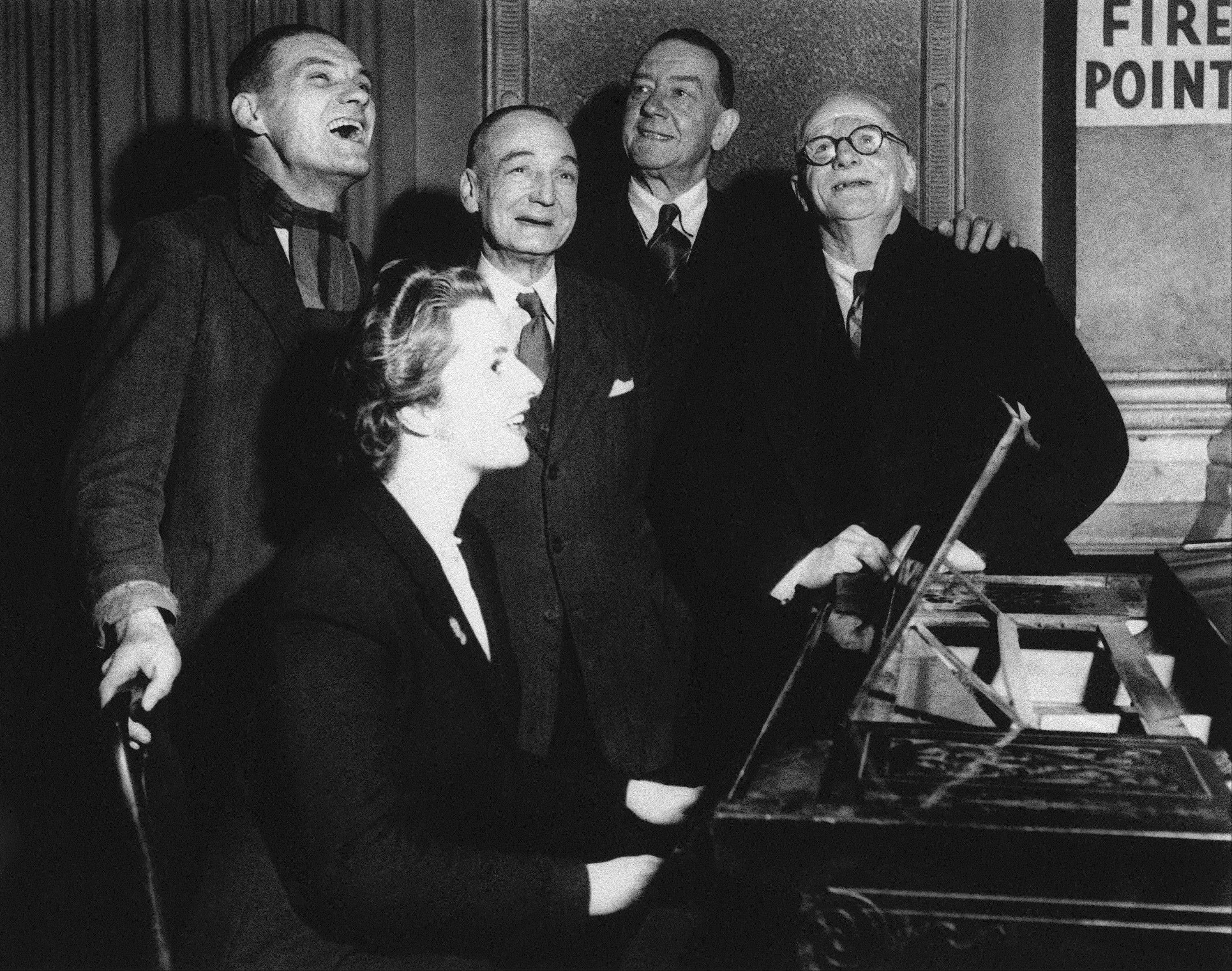 In a 1950 file photo, Conservative candidate at 23 years old and holder of an Oxford diploma, Margaret Roberts, later Thatcher, accompanies four voters on the piano in a sing along after a brief political argument in the bar of the Bull Inn, Dartford, England in 1950. Thatchers former spokesman, Tim Bell, said that the former British Prime Minister Margaret Thatcher died Monday morning, April 8, 2013, of a stroke. She was 87.