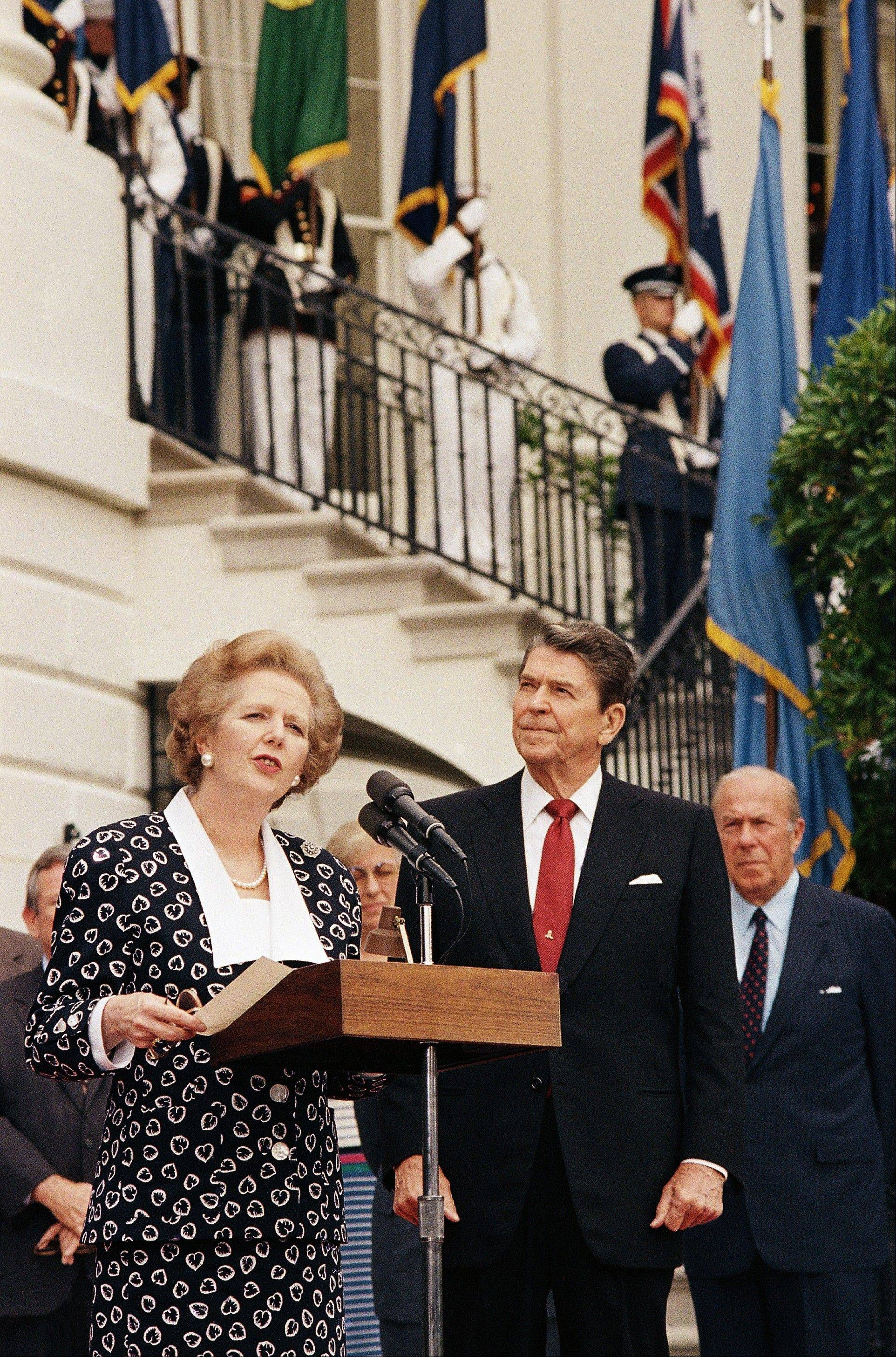 "In this July 18, 1987 file photo, President Ronald Reagan and Secretary of State George Shultz look on as British Prime Minister Margaret Thatcher reads a statement outside the White House in Washington. Ex-spokesman Tim Bell says that Thatcher has died. She was 87. Bell said the woman known to friends and foes as ""the Iron Lady"" passed away Monday morning, April 8, 2013."