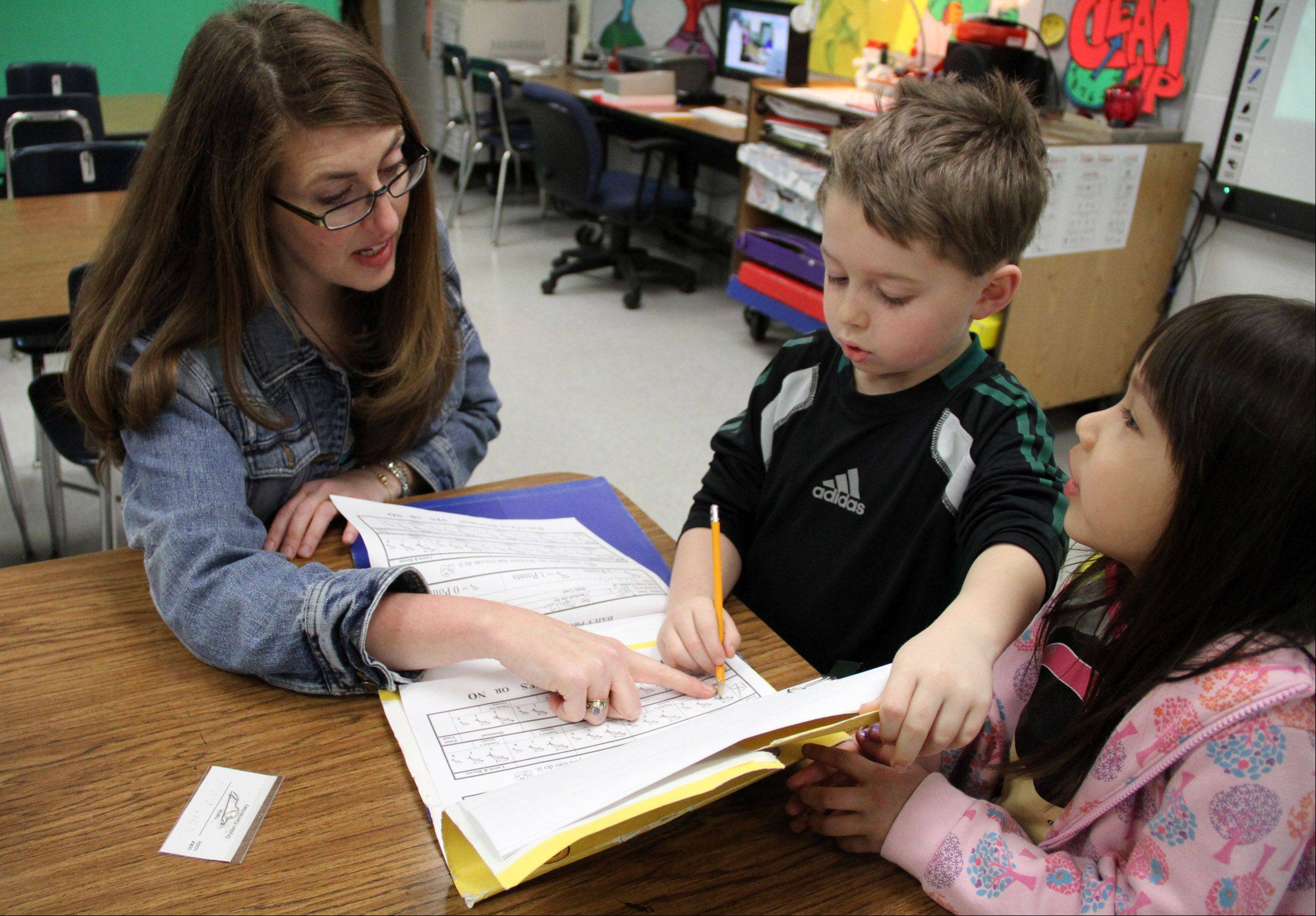 Dryden art teacher Tricia Fuglestad checks in first-graders Dylan Burnett, left, and Kaya Deleon before teaching her first class of the day.