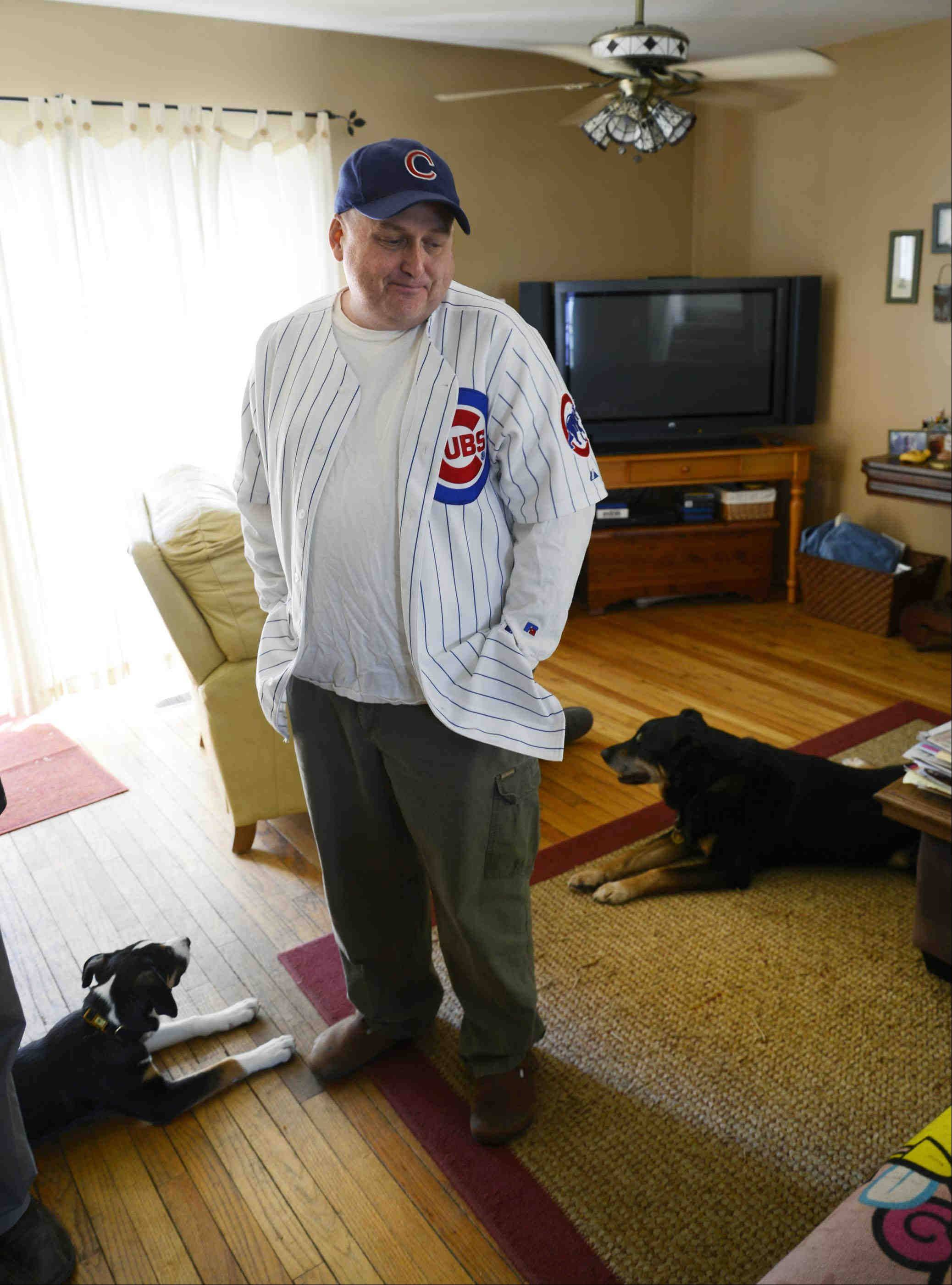 With dogs Homer, right, and Ralph at his feet, and his favorite Cubs hat on his head, Charley McLenna of Lake in the Hills sees reasons for hope.