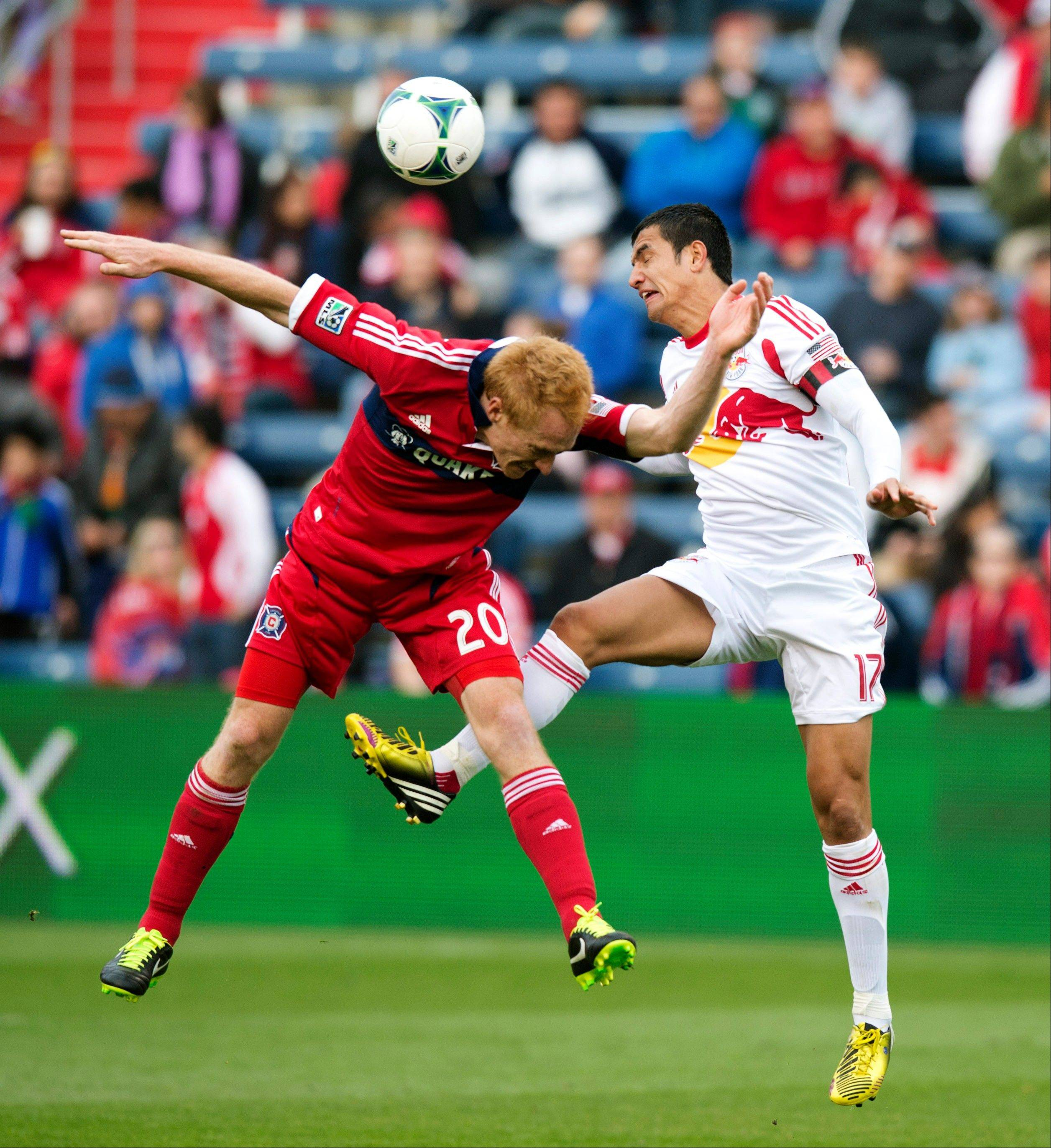 In this photo provided by the Chicago Fire, New York Red Bulls forward Tim Cahill, right, and Chicago Fire midfielder Jeff Larentowicz go for the ball during the second half of an MLS soccer match, Sunday, April 7, 2013, in Bridgeview, Ill. The Fire won 3-1.