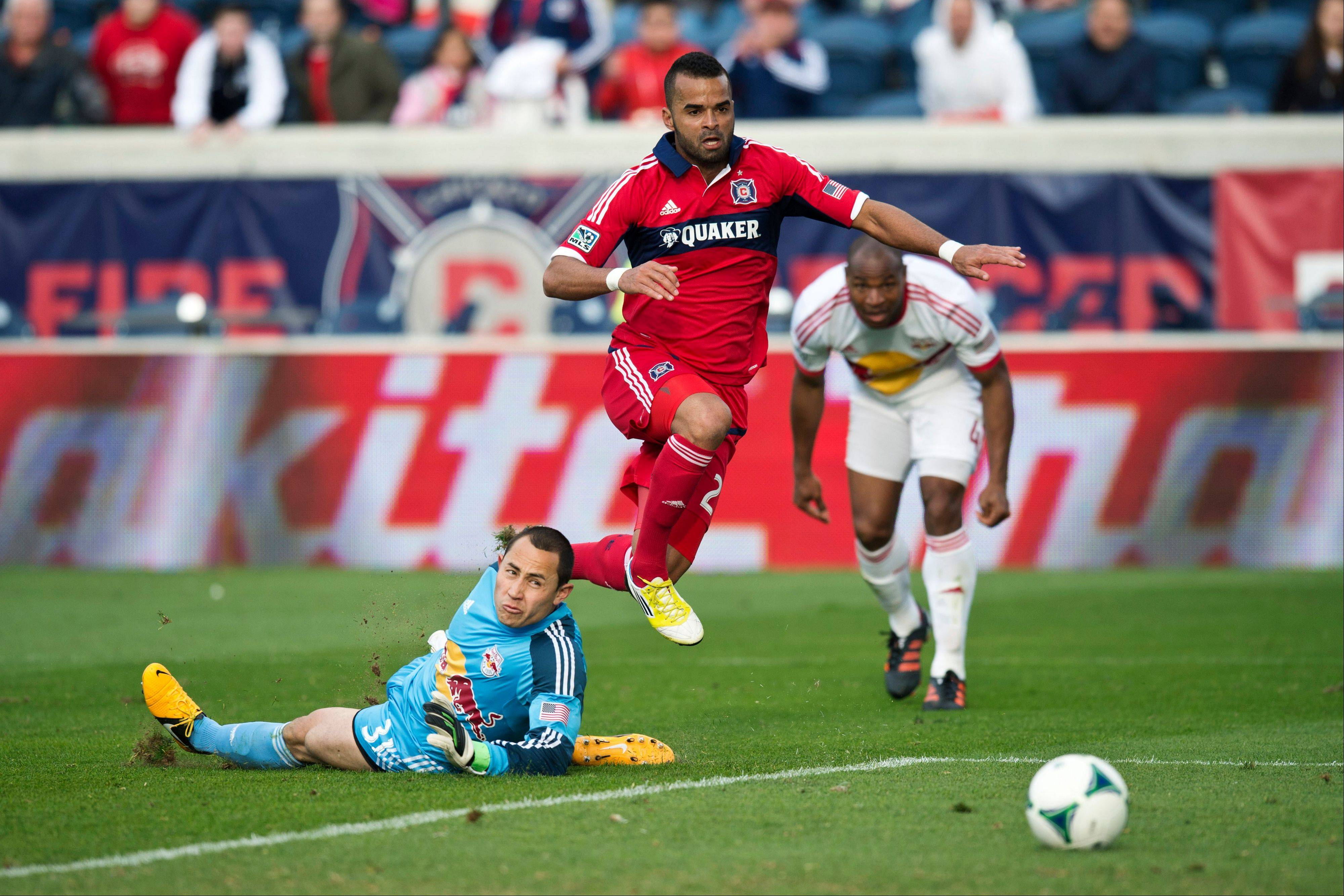 In this photo provided by the Chicago Fire, Chicago Fire forward Maicon Santos, center, scores past New York Red Bulls goalkeeper Luis Robles, left, as defender Jamison Olave watches during the second half of an MLS soccer match, Sunday, April 7, 2013, in Bridgeview, Ill. The Fire won 3-1.
