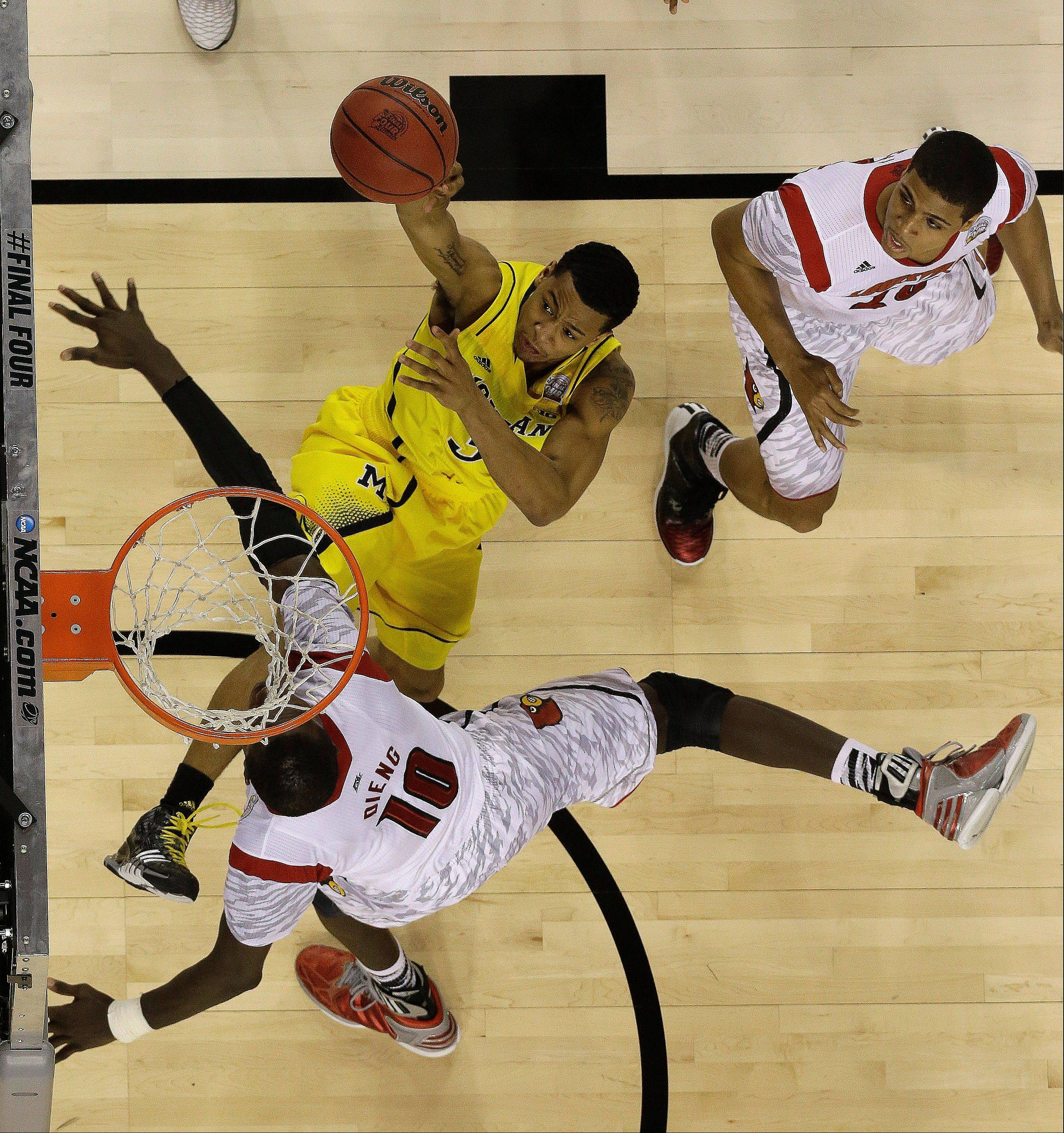 Michigan guard Trey Burke (3) shoots against Louisville center Gorgui Dieng (10) during the second half of the NCAA Final Four tournament college basketball championship game Monday, April 8, 2013, in Atlanta.