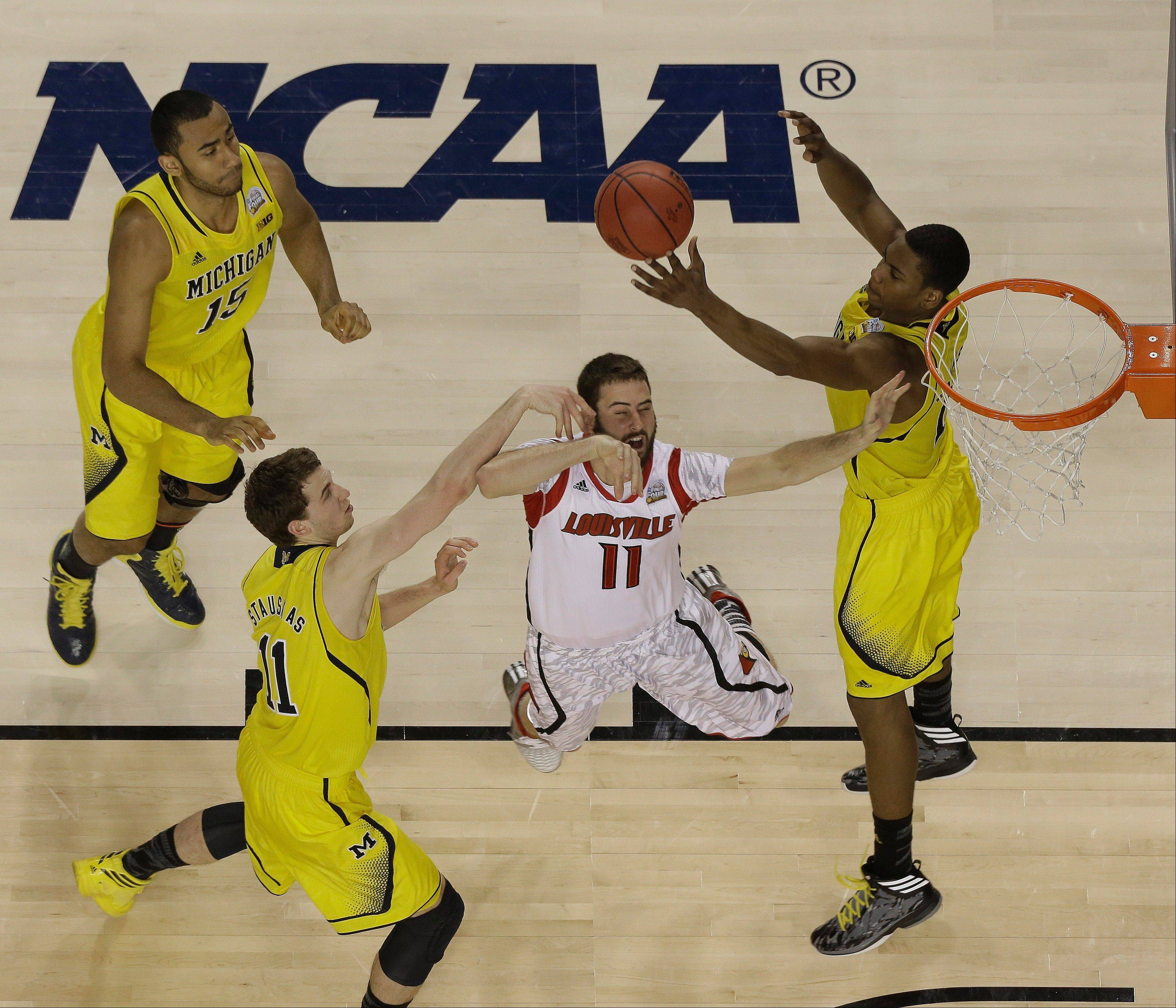 Louisville guard/forward Luke Hancock (11) loses the ball as Michigan forward Glenn Robinson III (1) and Michigan guard Nik Stauskas (11) defend during the first half of the NCAA Final Four tournament college basketball championship game Monday, April 8, 2013, in Atlanta.