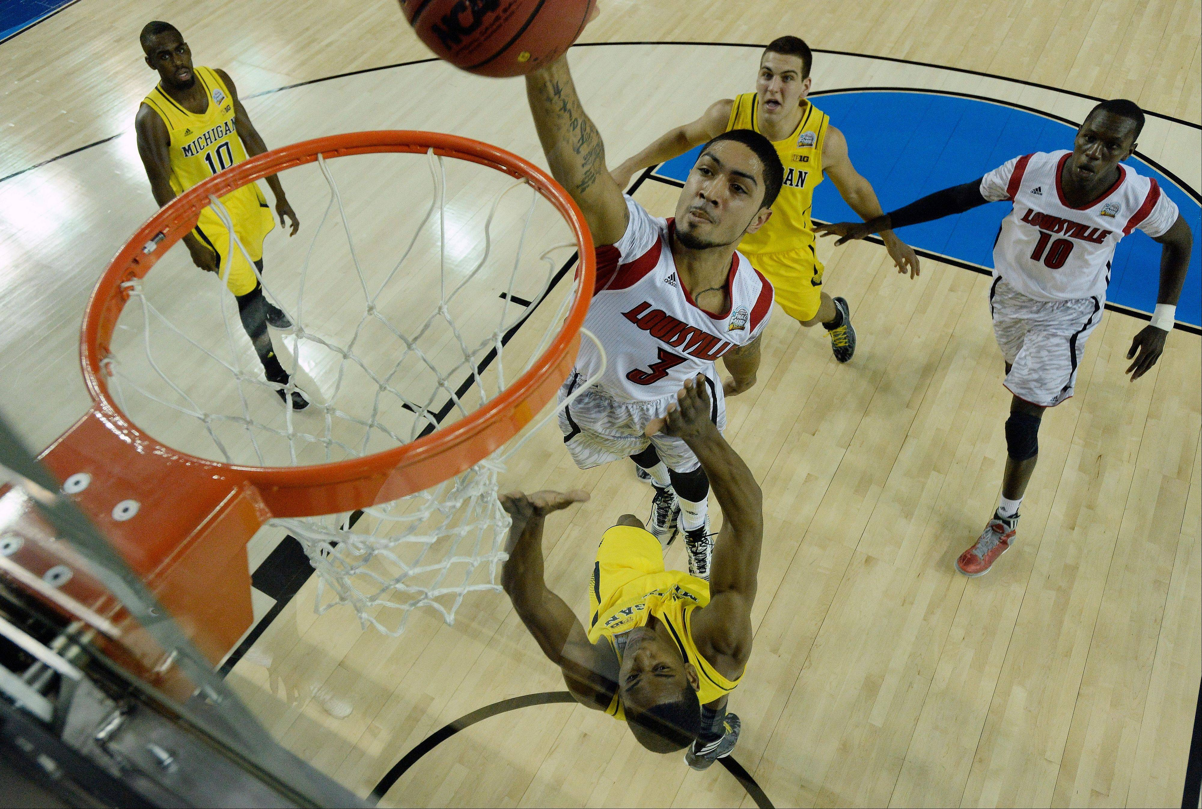 Louisville guard Peyton Siva (3) shoots against a Michigan defense during the first half of the NCAA Final Four tournament college basketball championship game Monday, April 8, 2013, in Atlanta.